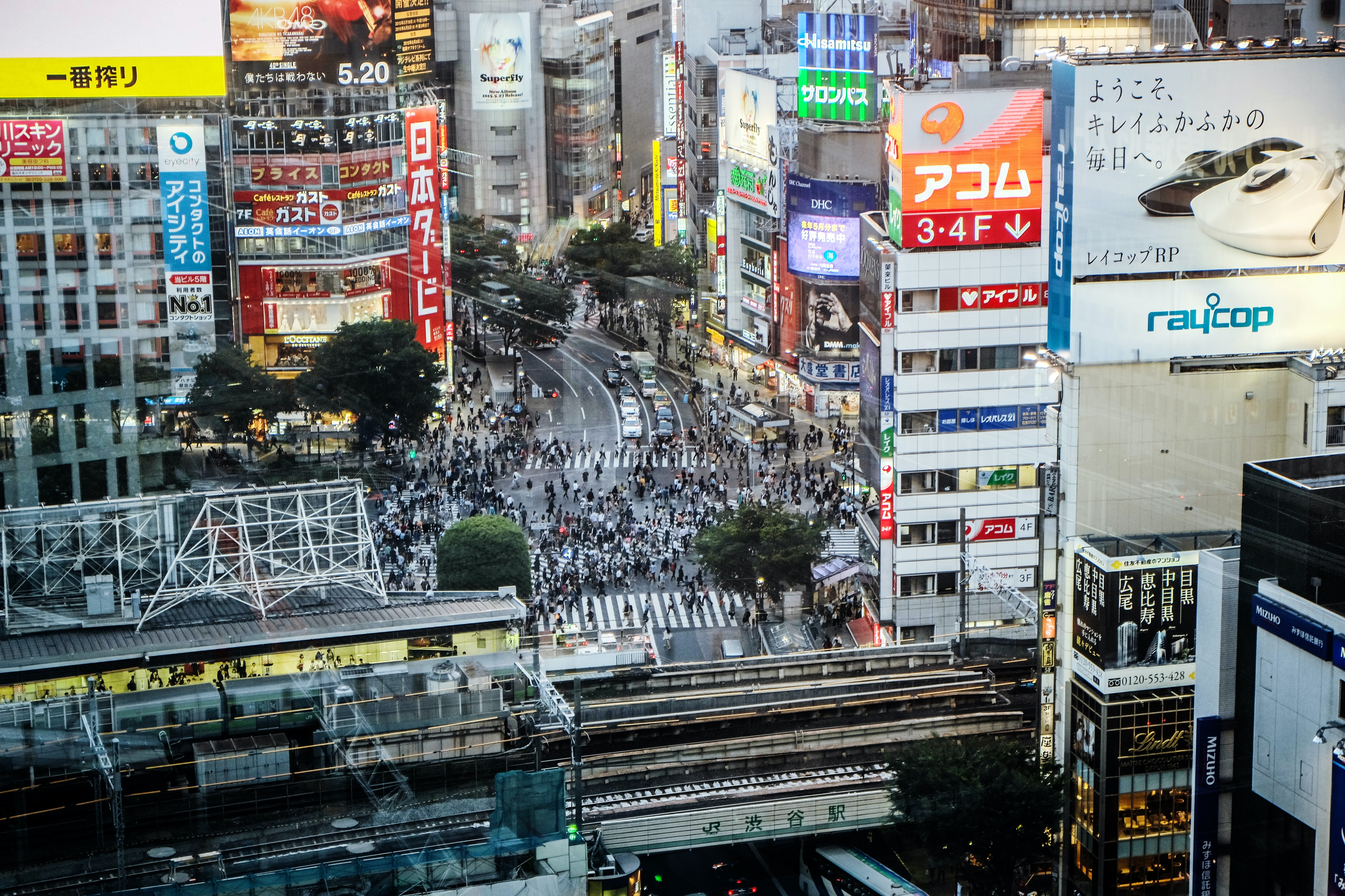 A distant shot of a crowded intersection surrounded by colorful advertisements