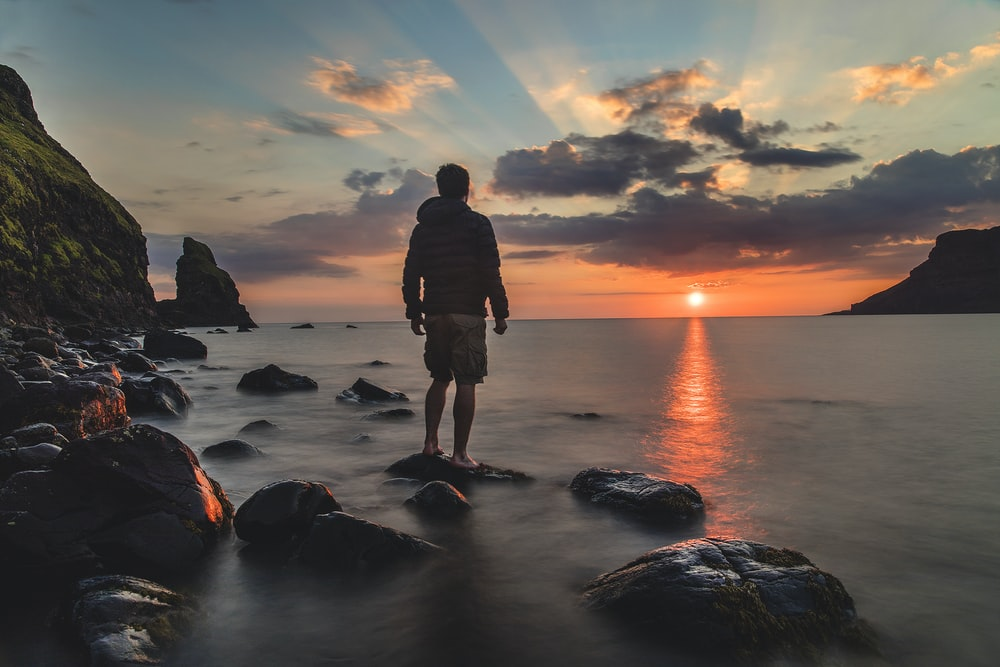 man standing on stone looking at sunset