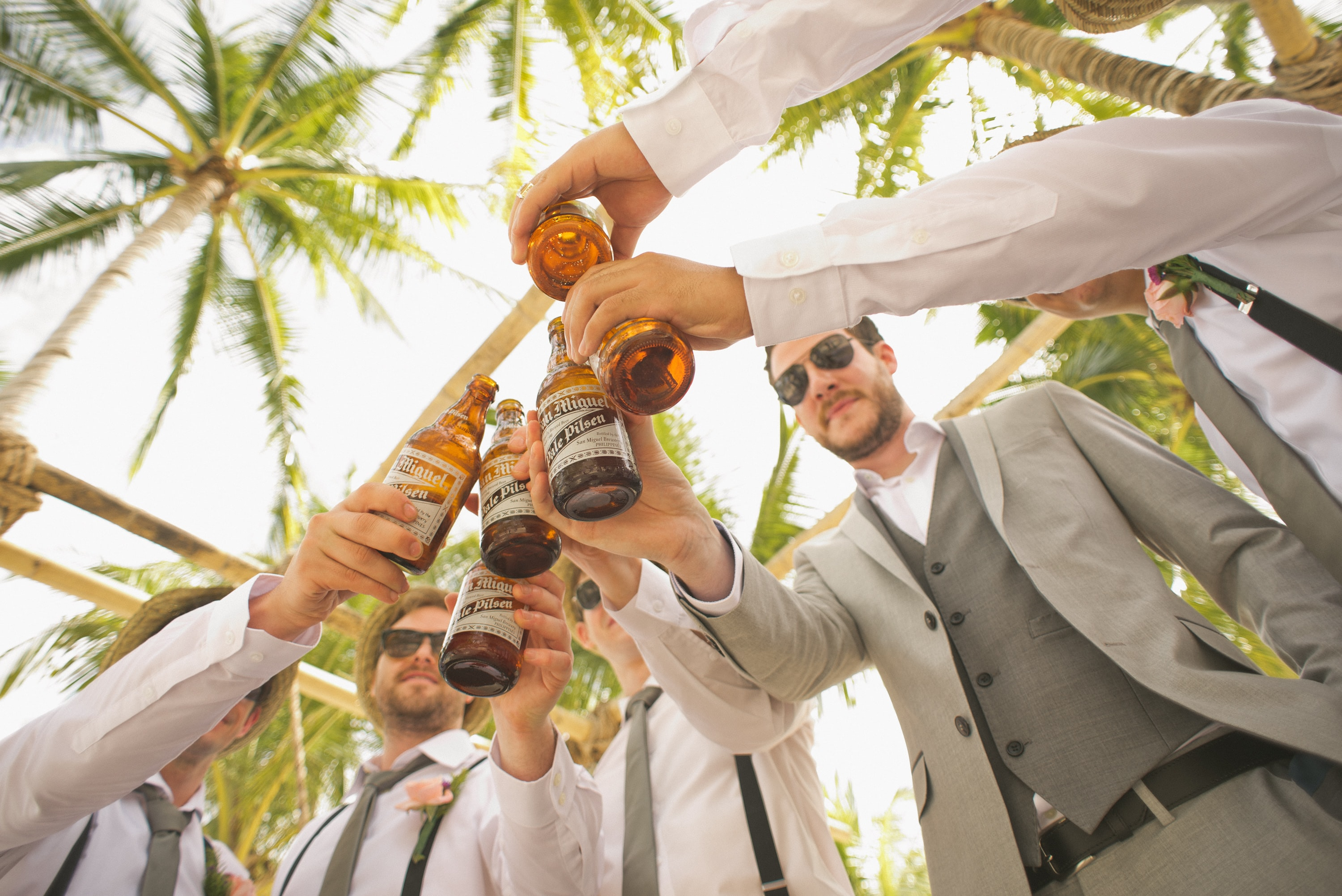 low angle of men holding beer bottles and having a toast