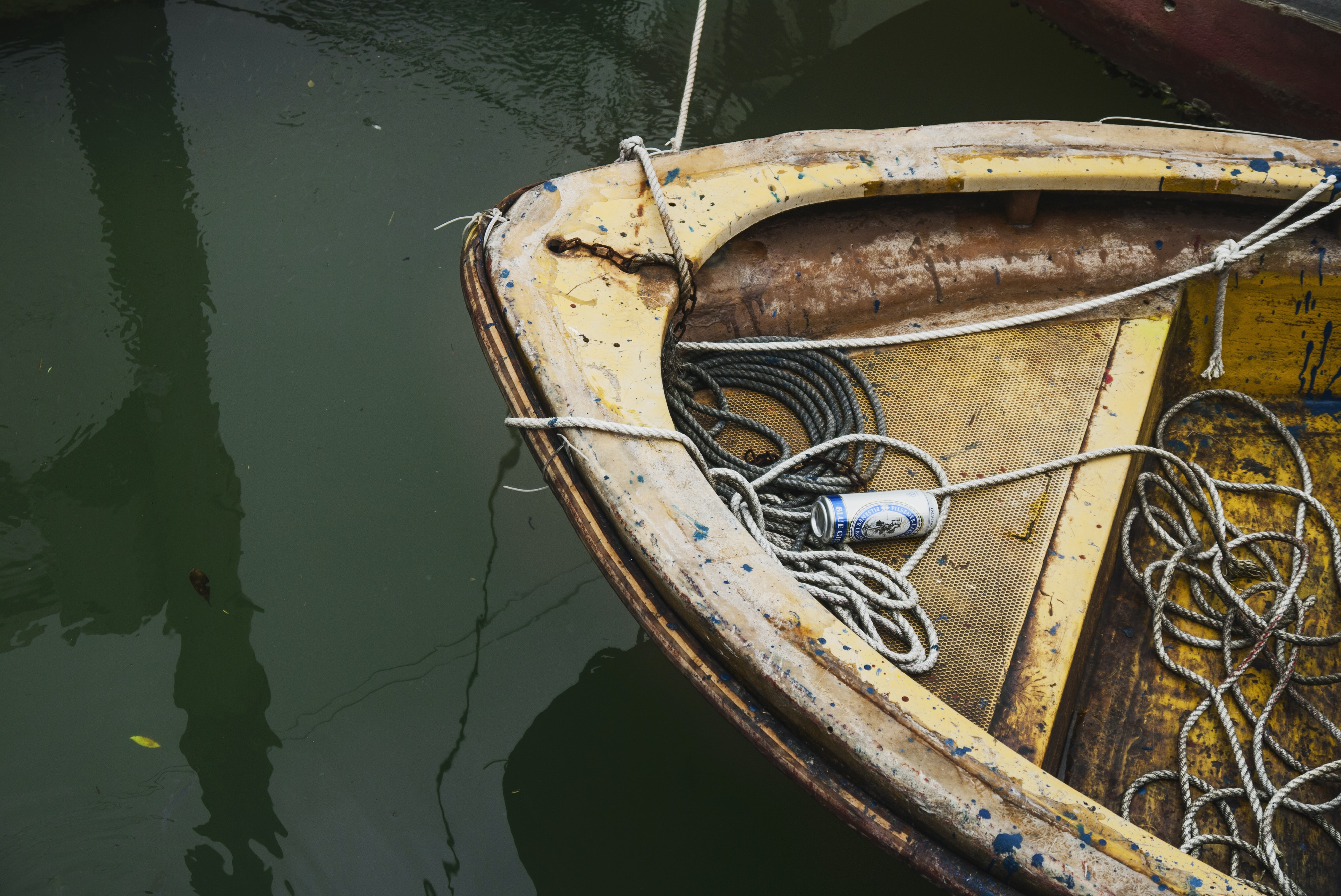 A rusty old boat on the river tied with rope and a beer inside it the mooring, tai O