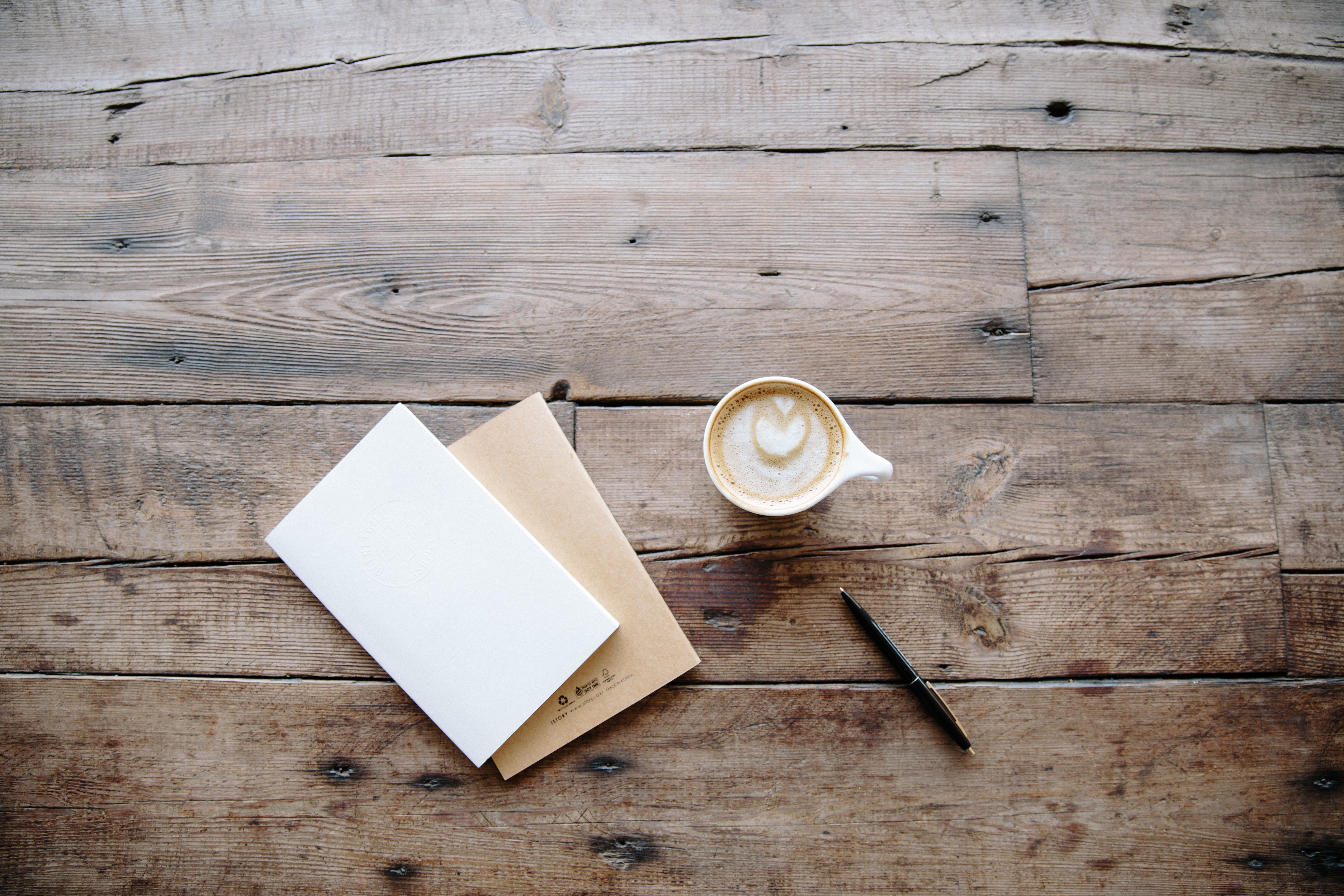 An overhead shot of a cup of coffee, a pen and two notebooks on a wooden surface