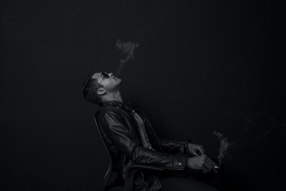 grayscale photo of man with cigarette stick