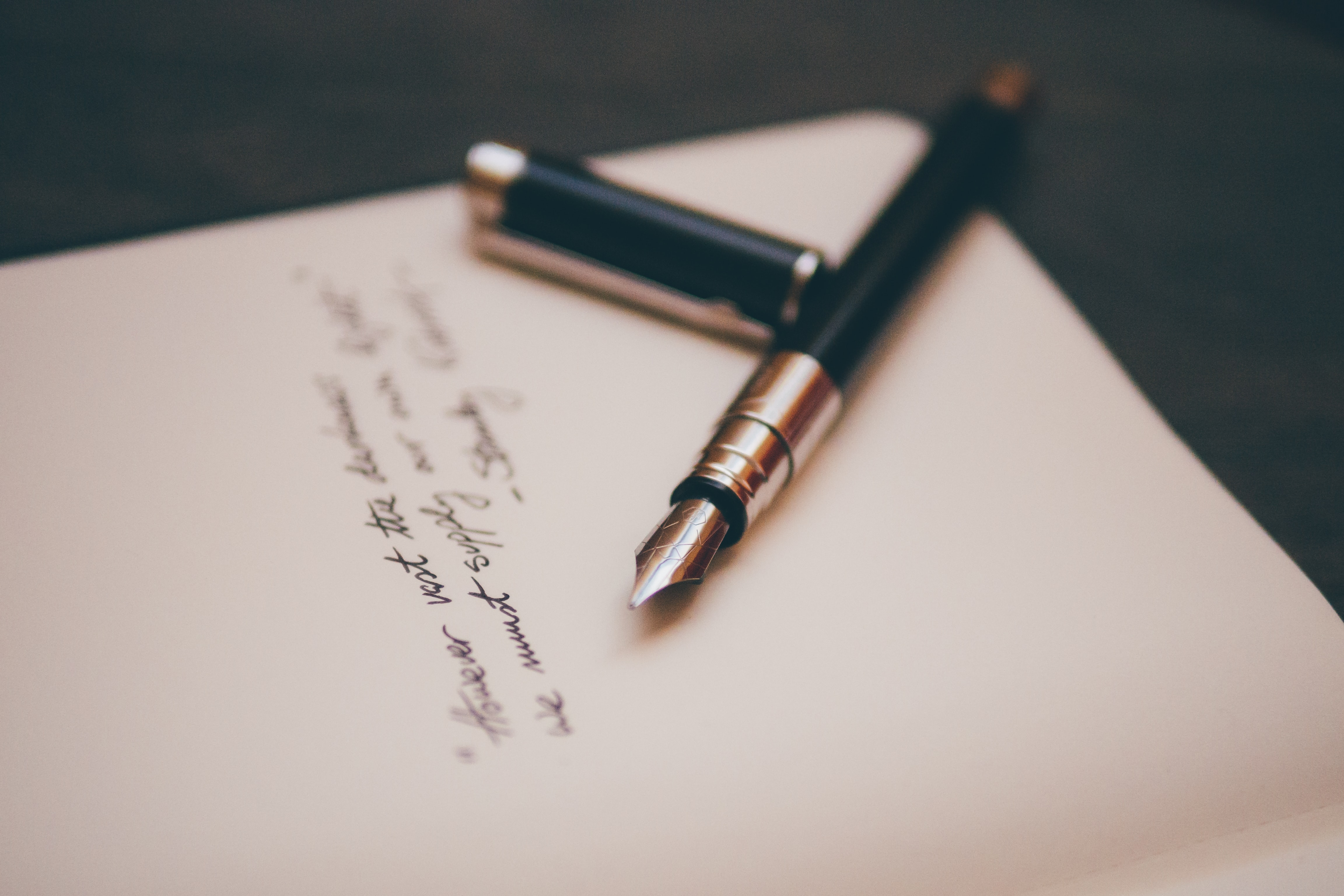 A fountain pen near cursive writing on white stationery