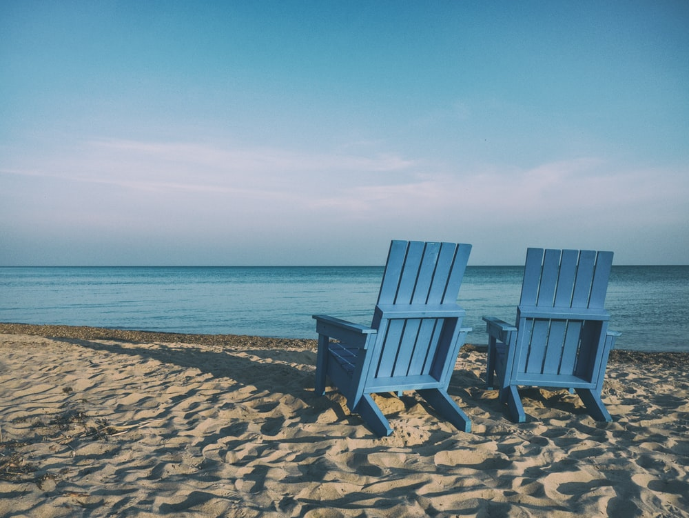 Pair of wooden blue beach chairs on the sand beach