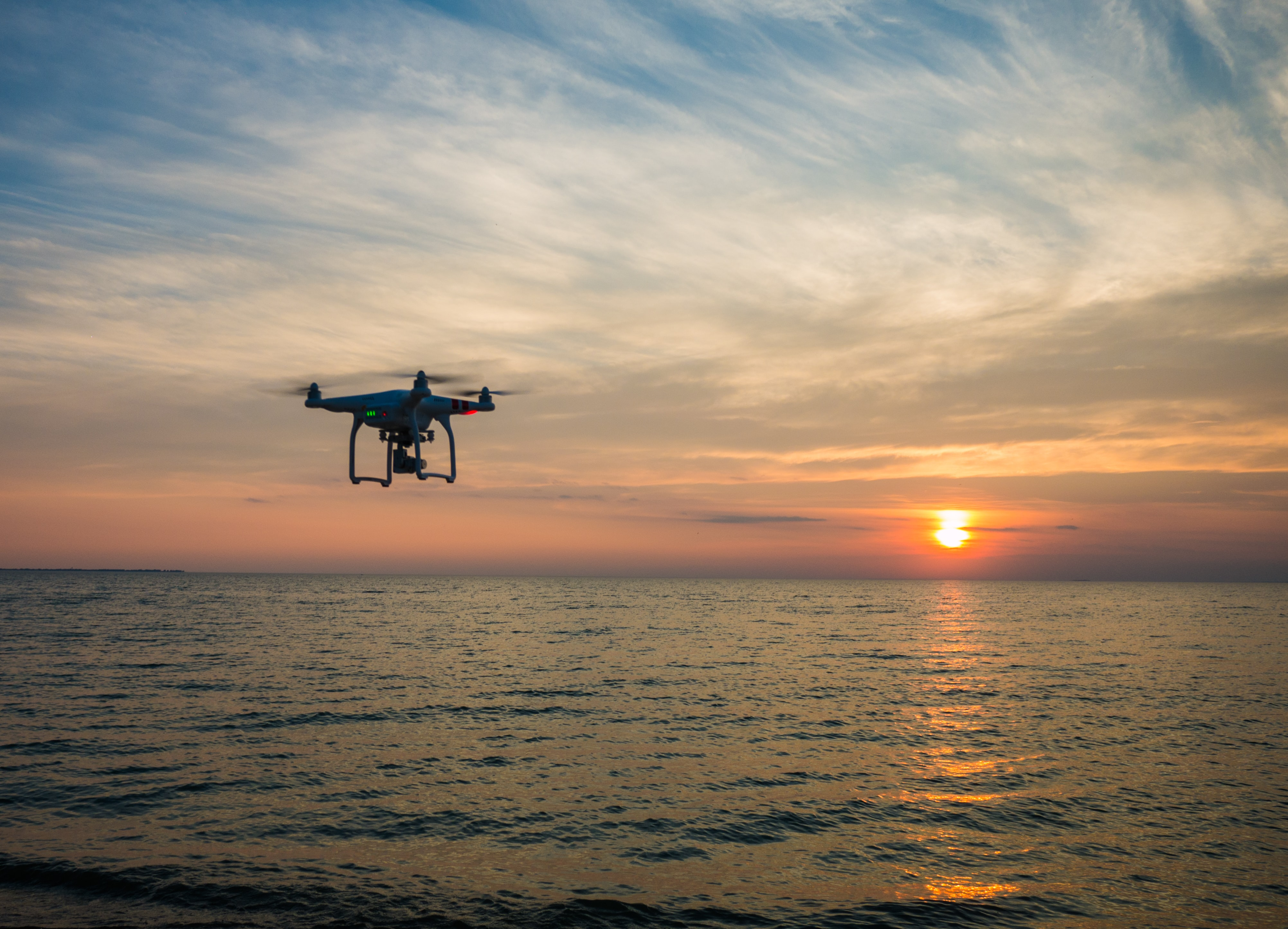 A drone flying over the sea capturing a cloudy orange sunset