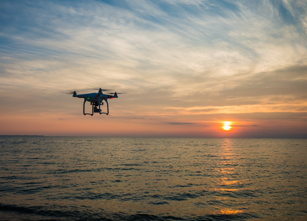 quadcopter flying over body of water