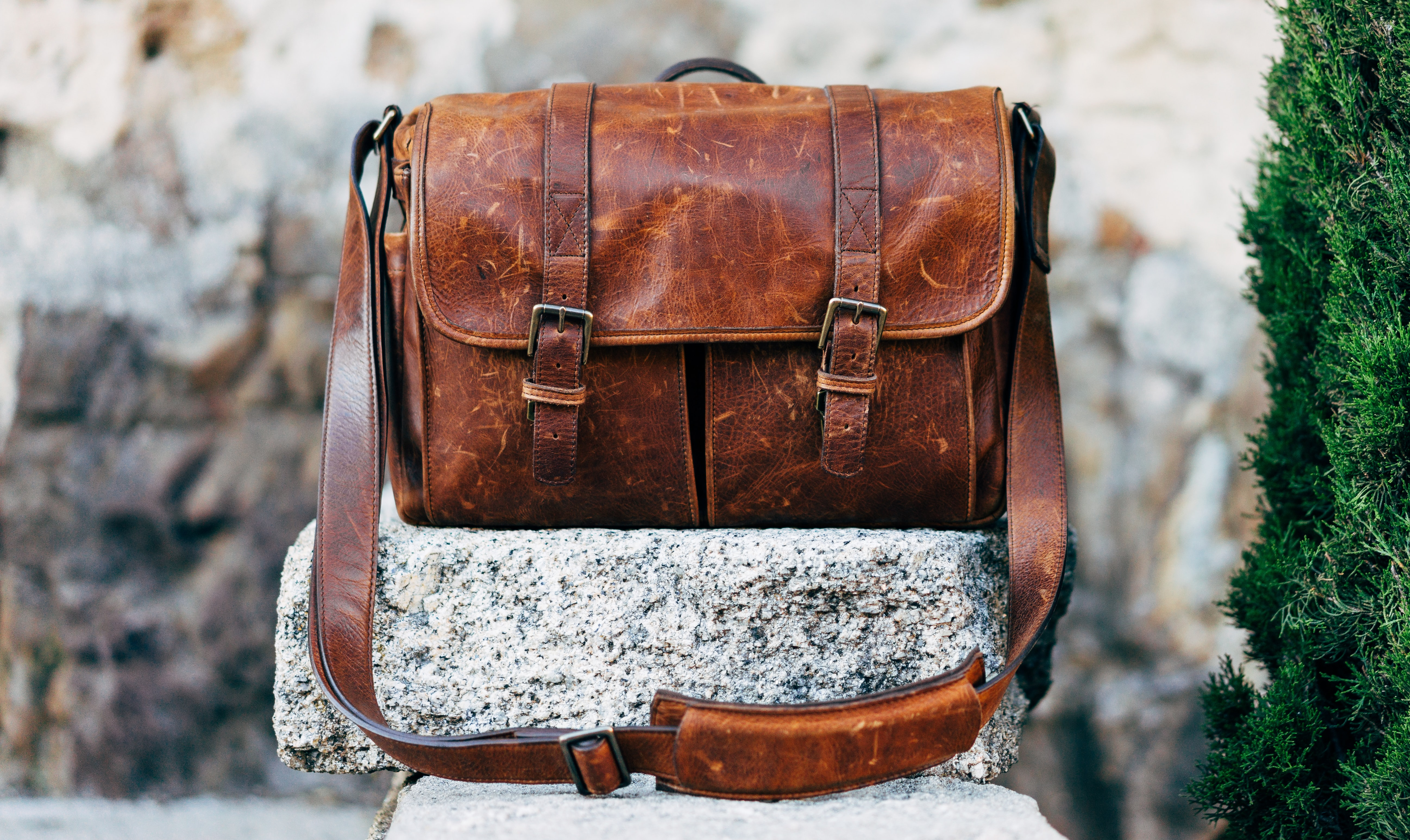 brown leather satchel bag on gray concrete surface near green plant at daytime