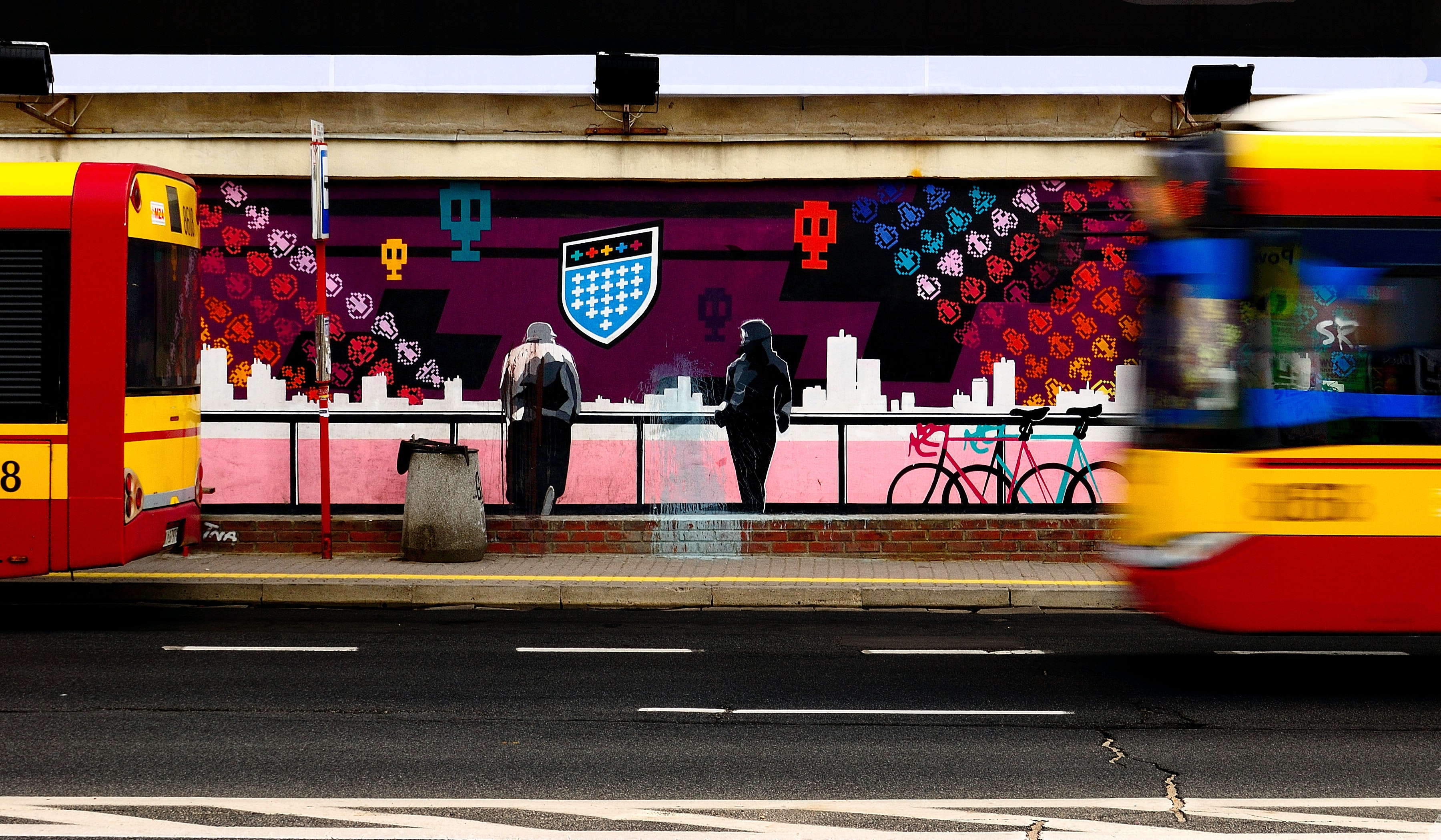 People standing against railing with public transport passing and colorful space invaders graffiti on wall