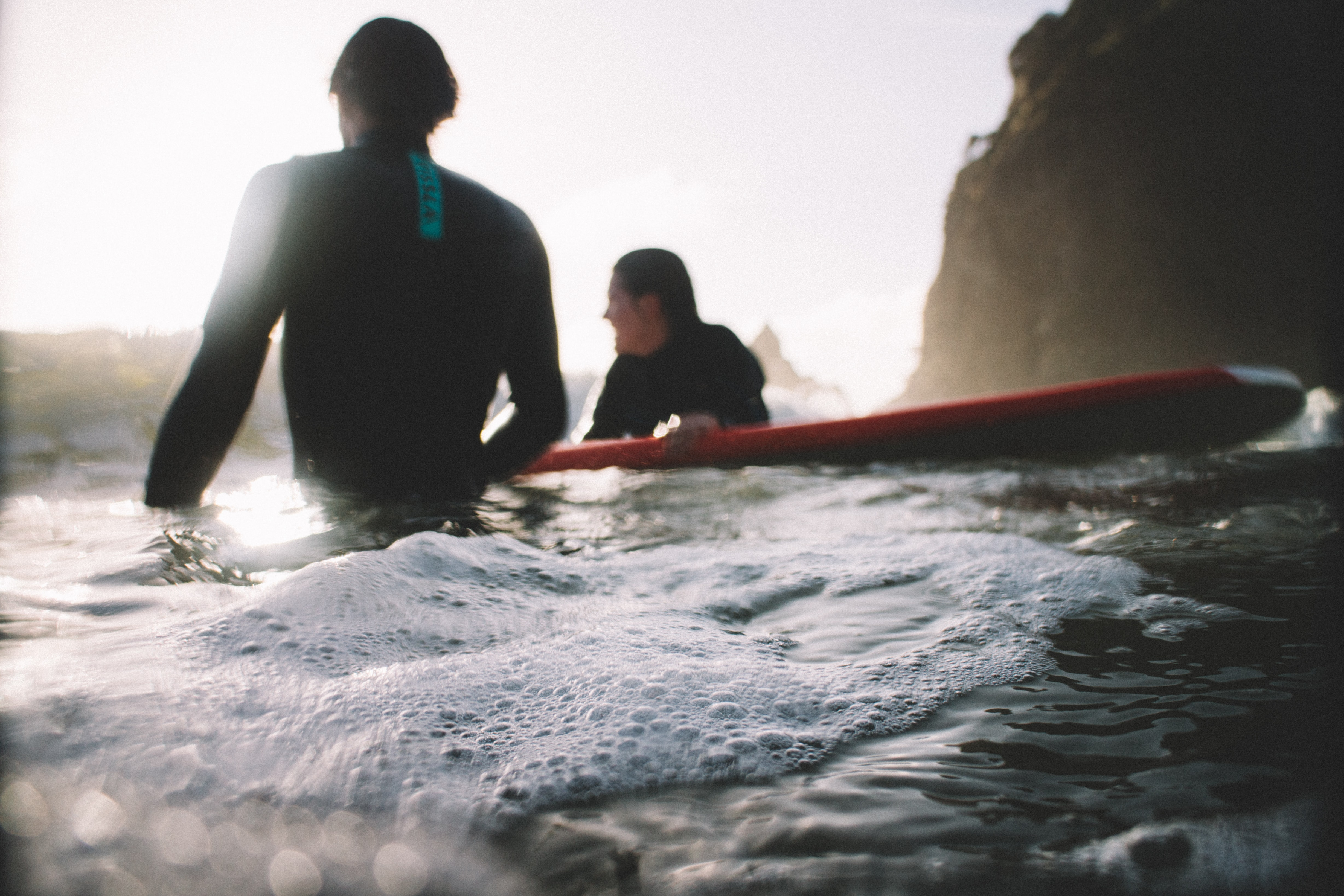 Two surfers in wetsuits with a surfboard in the foamy ocean at Piha Beach