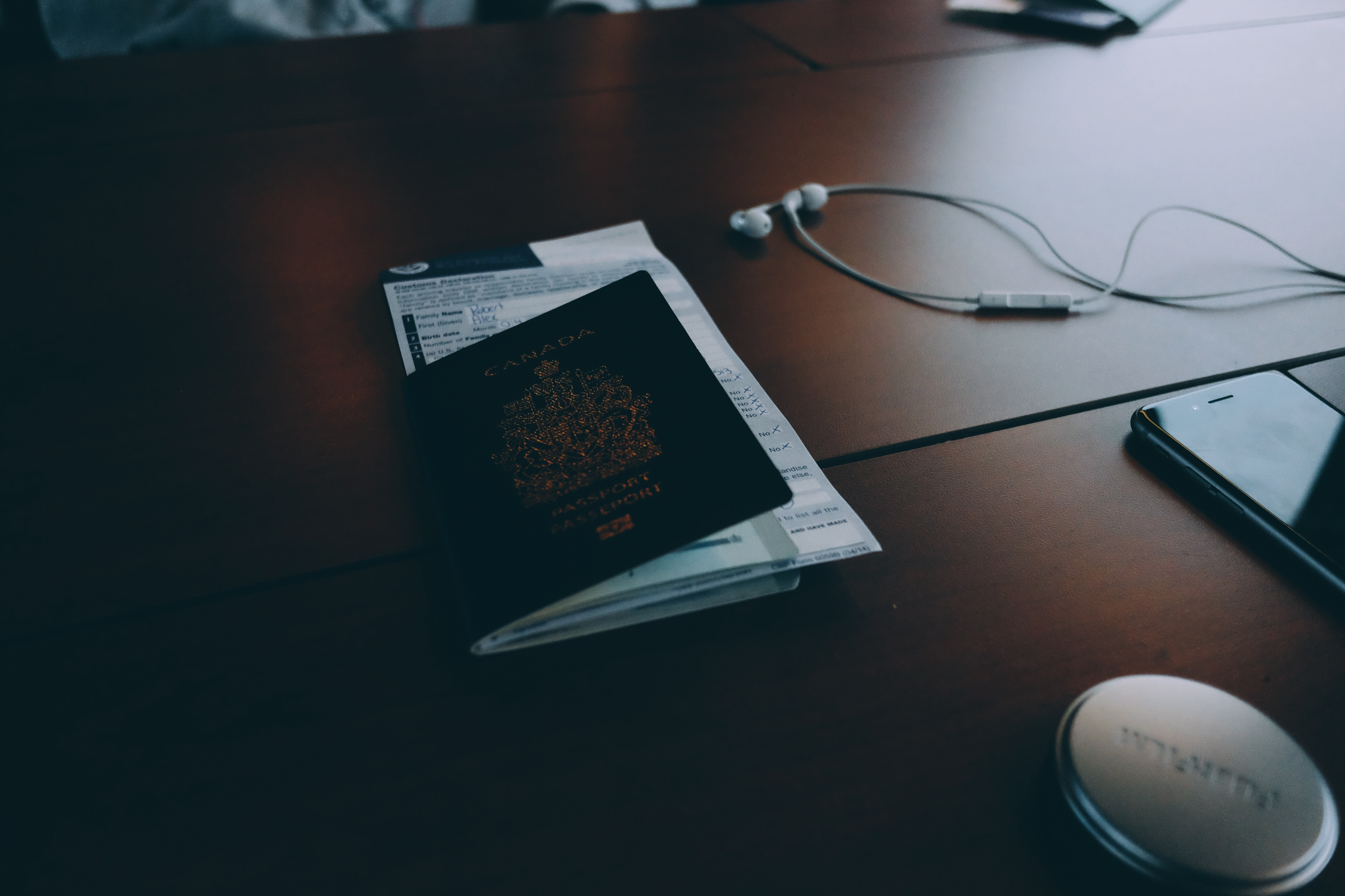 Passport and documents on desk near phone and headphones