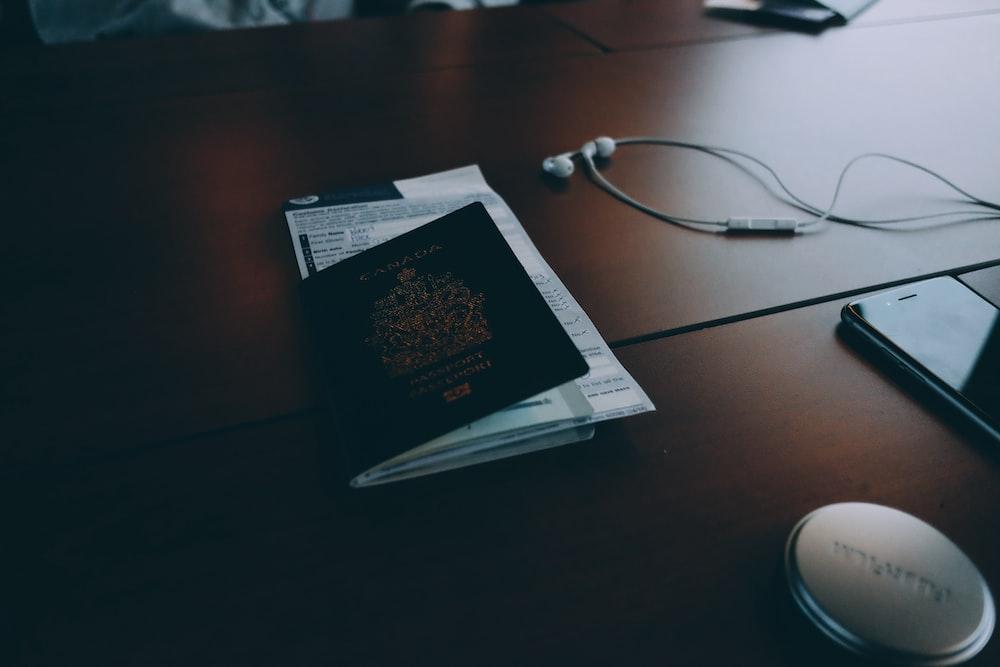 passport beside earphones on surface