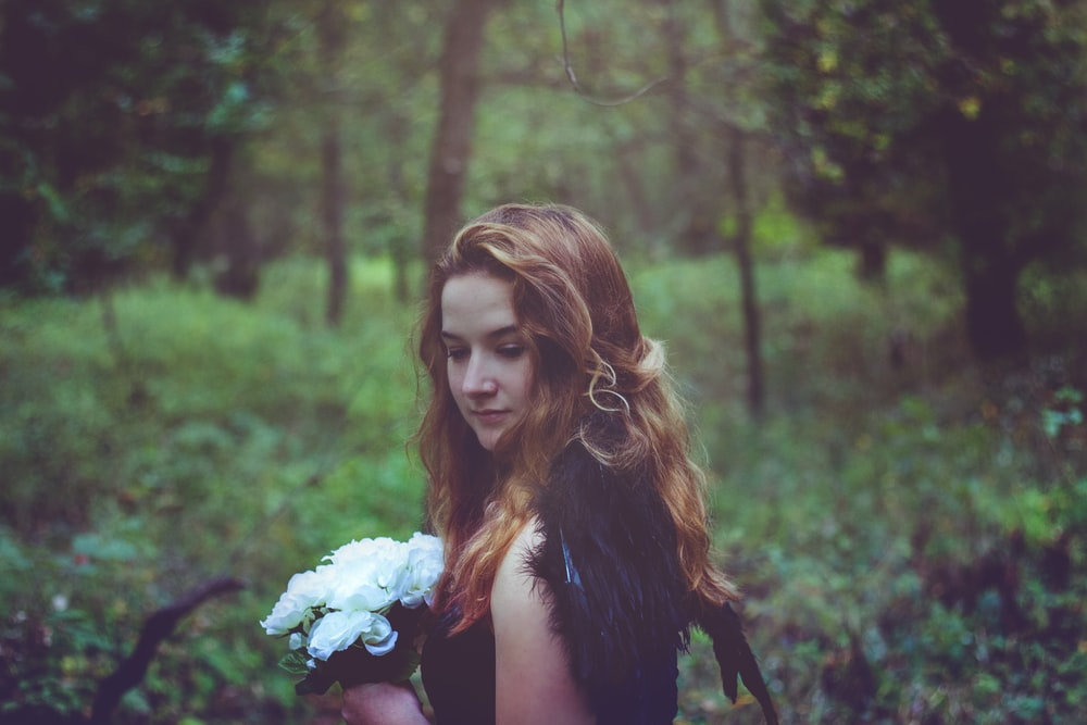 shallow focus photo of woman in black top holding white flowers