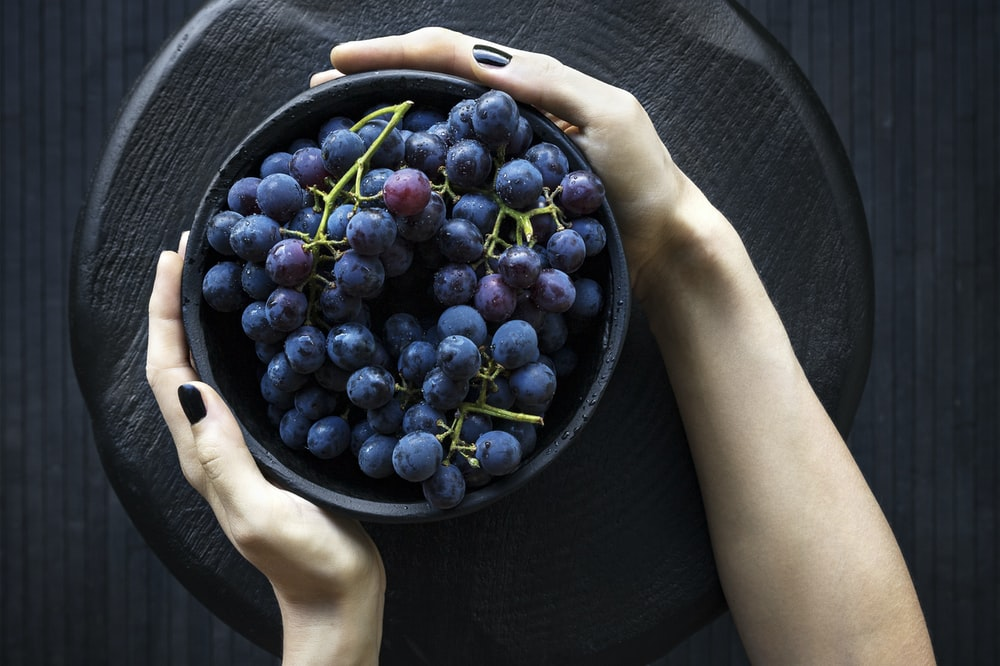 person holding bowl of grapes