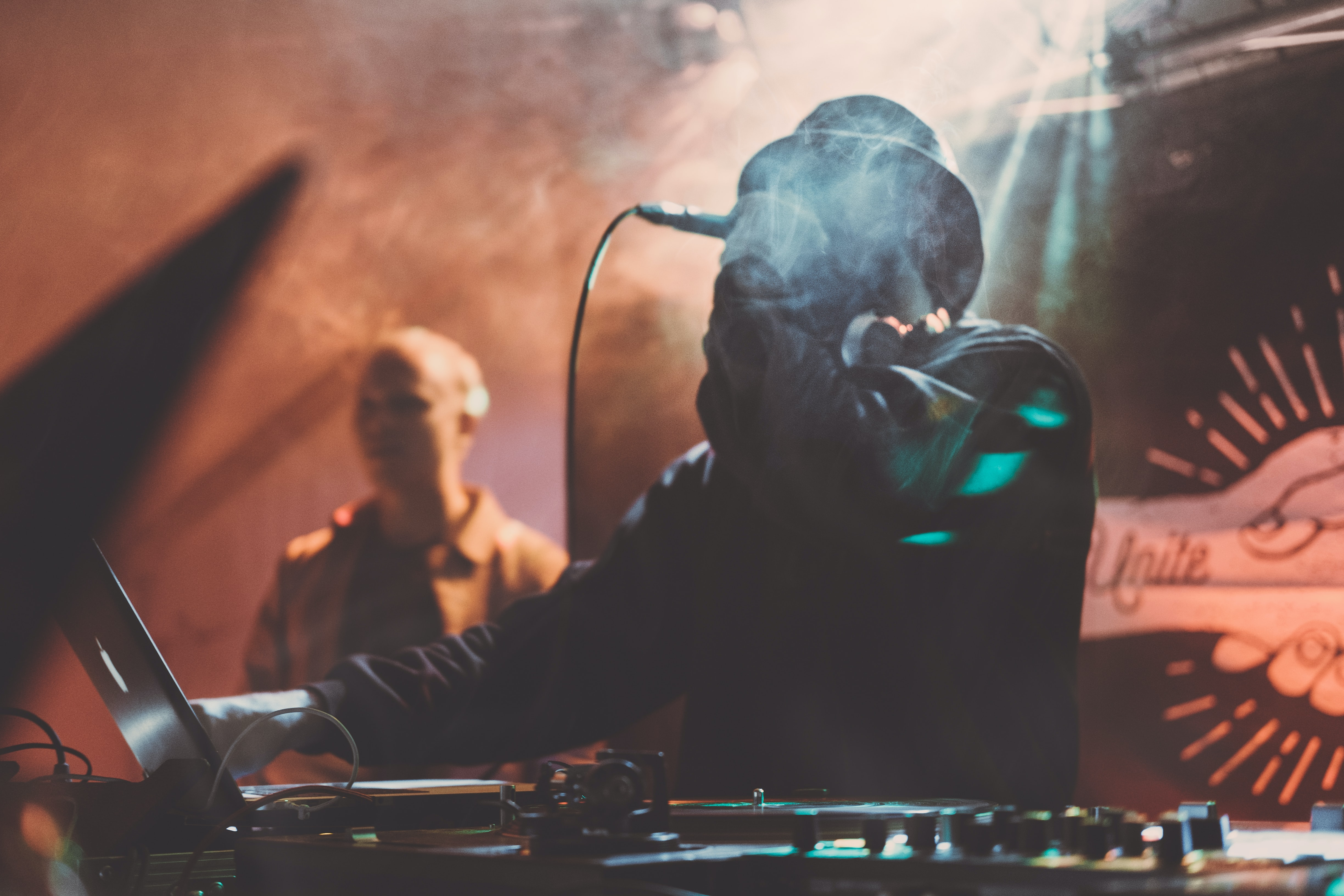 man holding dynamics microphone in front of DJ turn table