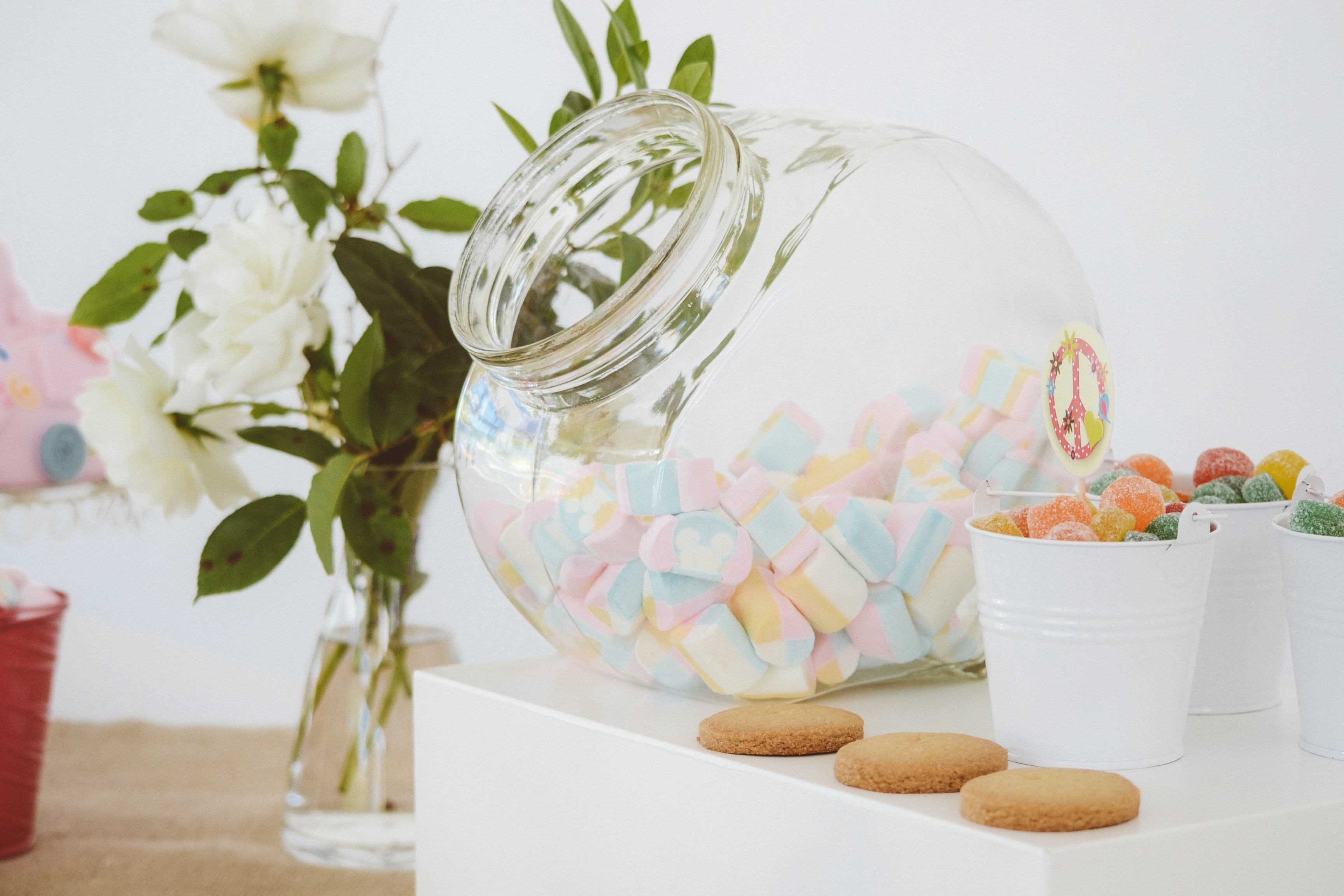 A large jar full of colorful marshmallows next to cookies and cups of candy