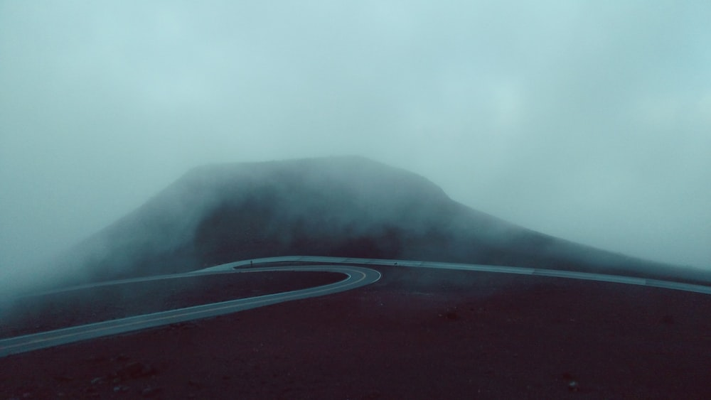 concrete road near mountain during foggy weather