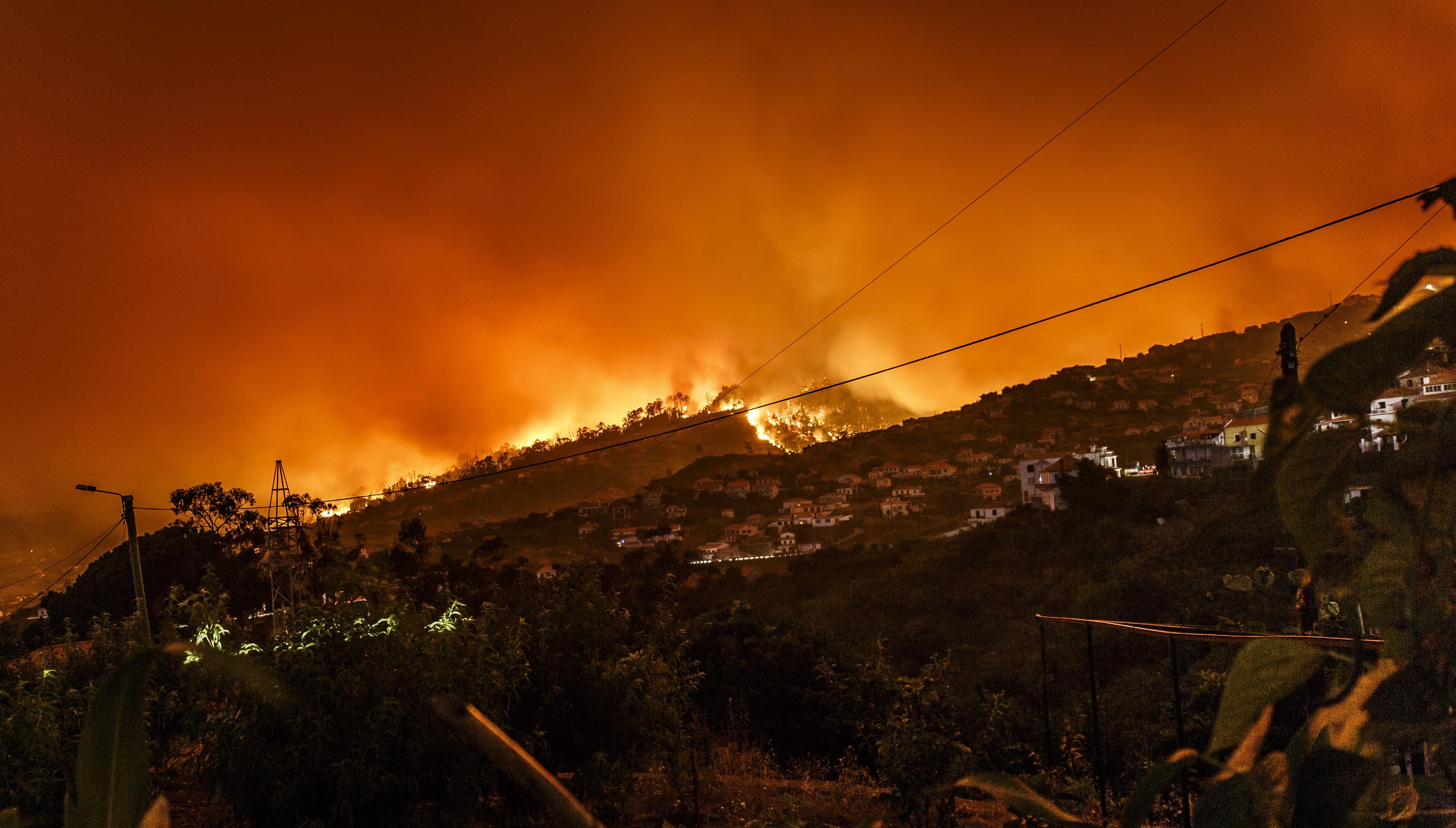 Forest fire creates an orange silhouette around a hill in Estreito da Calheta during evening