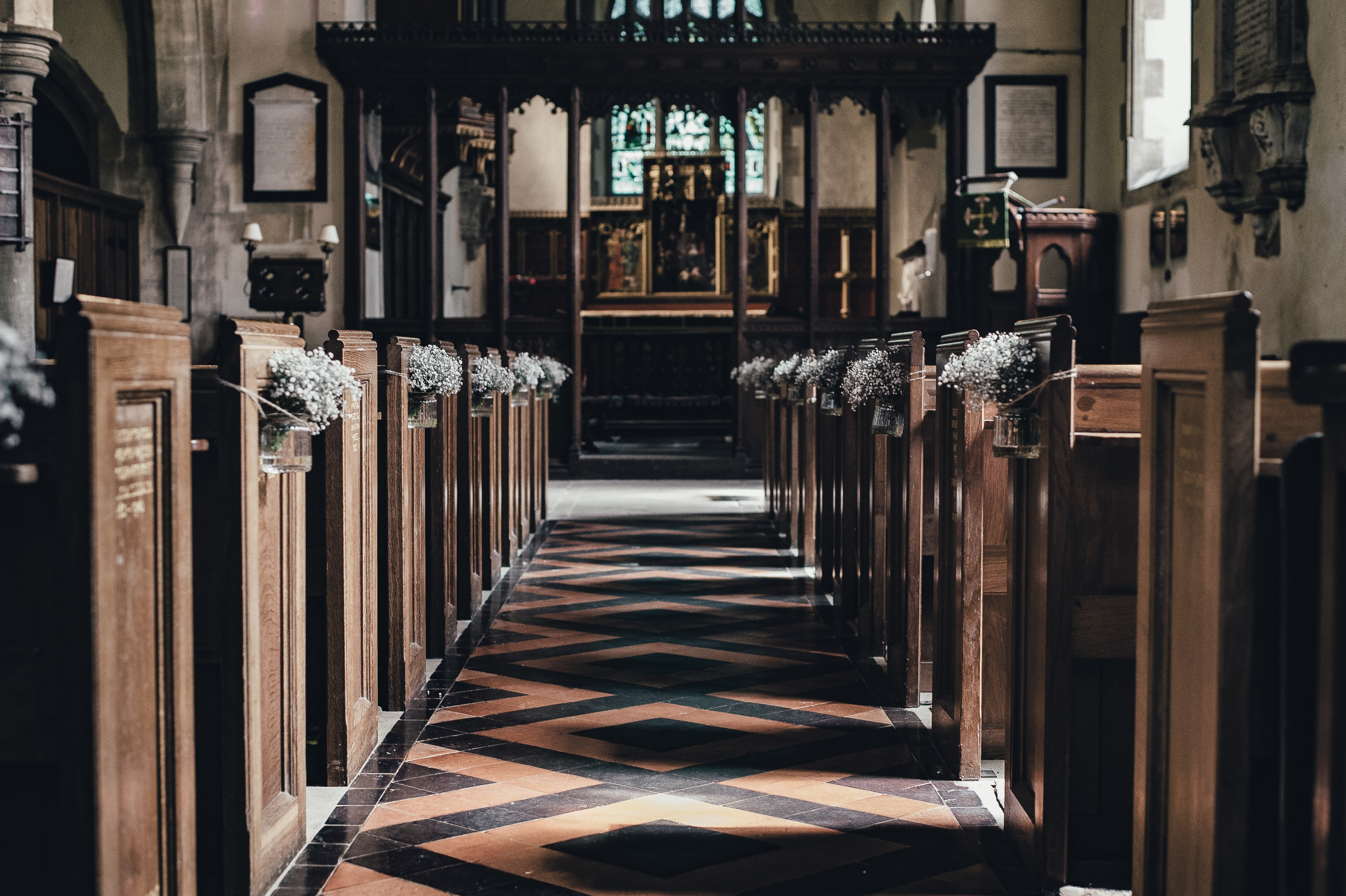 Church aisle with wooden benches and tile floor leading towards the wedding altar