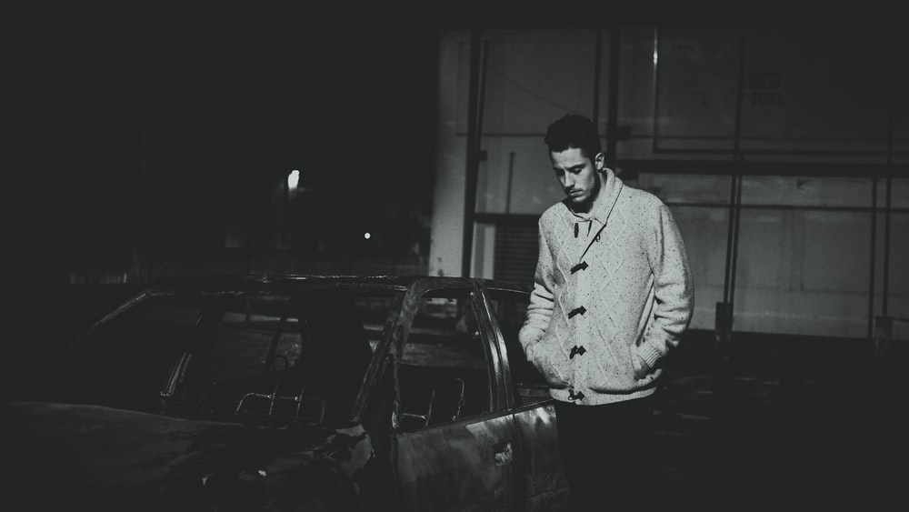 grayscale photo of man standing beside car