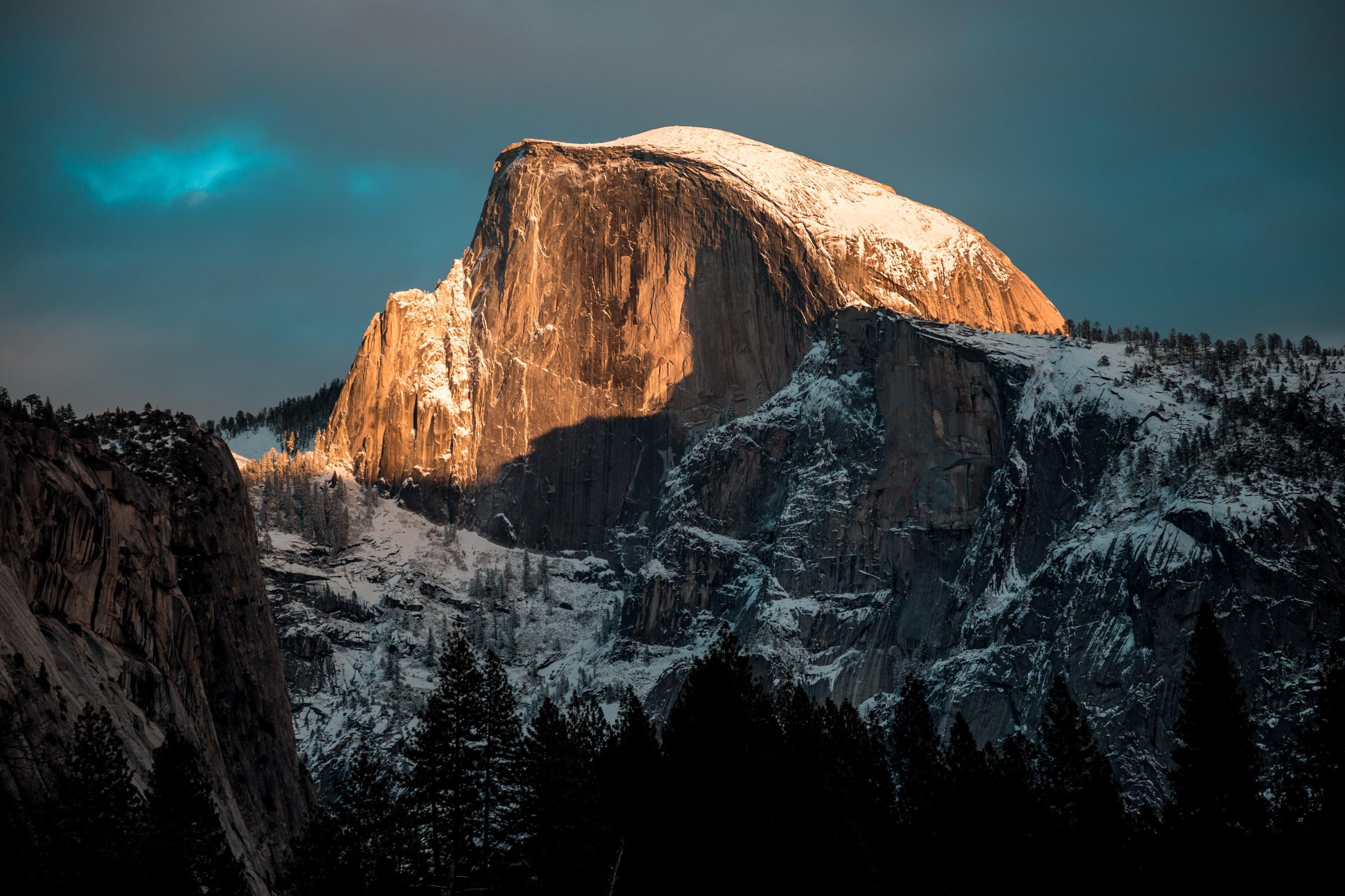 The sun lighting up a snowcapped Half Dome peak at California's Yosemite National Park