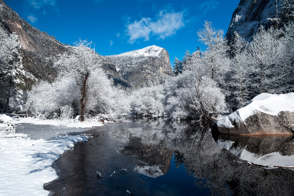 snow capped mountain near river at daytime