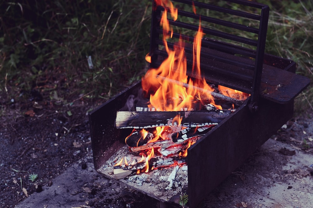 brown metal grill with firing firewood