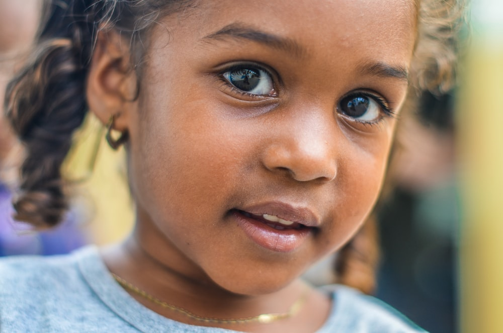 close-up photography of child wearing gray top