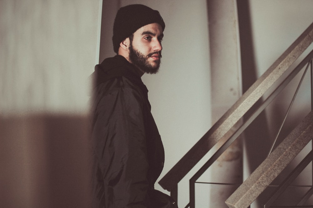 Man with a beard wearing a hat walking up an industrial staircase