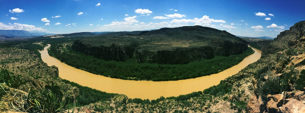 aerial photography of river beside green mountain during daytime