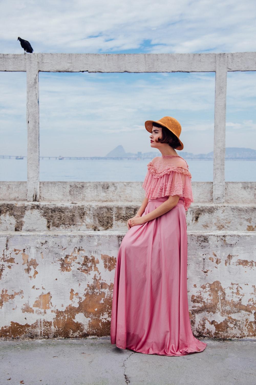 woman wearing pink dress standing next to white wall
