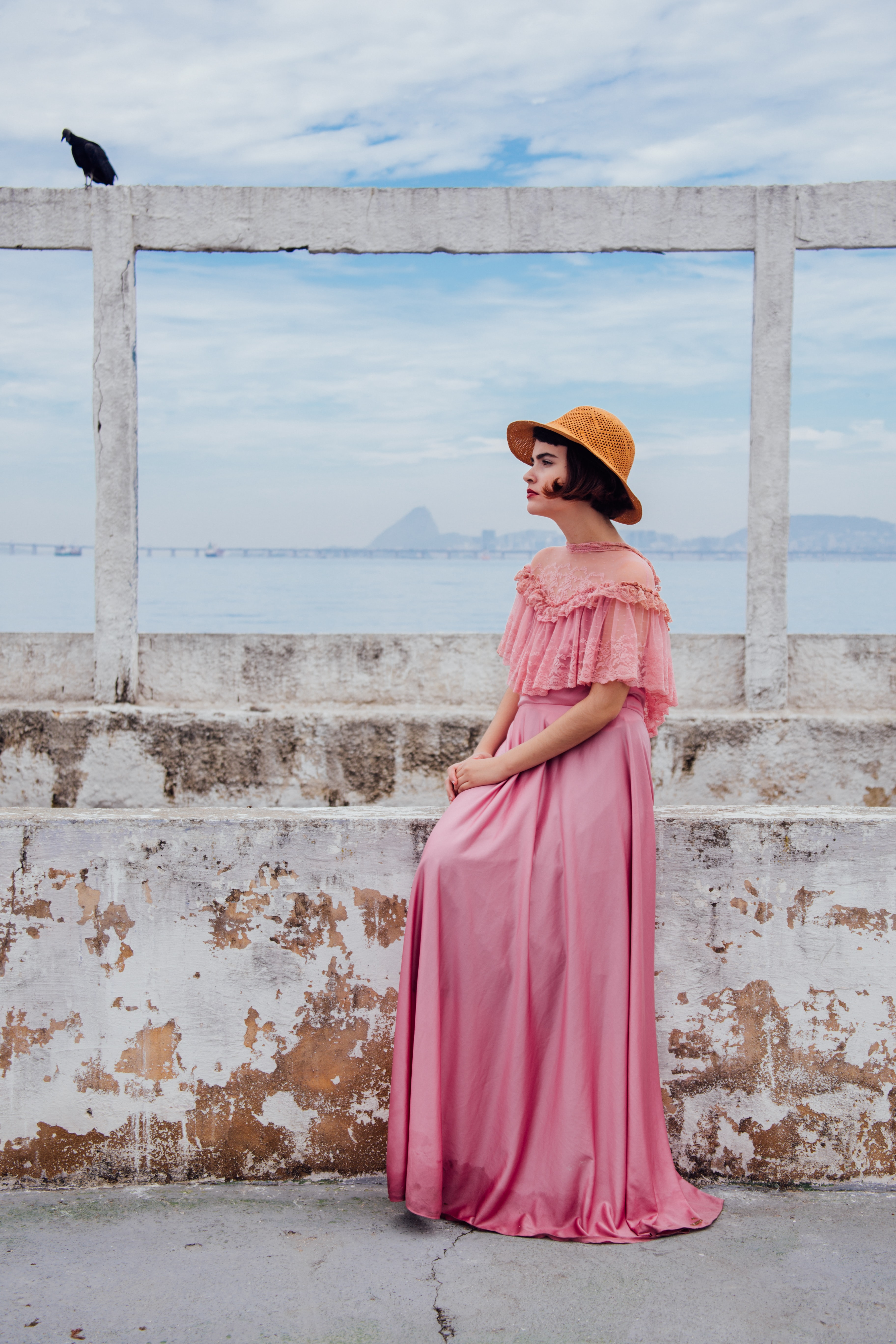 woman wearing pink dress standing next to white wall