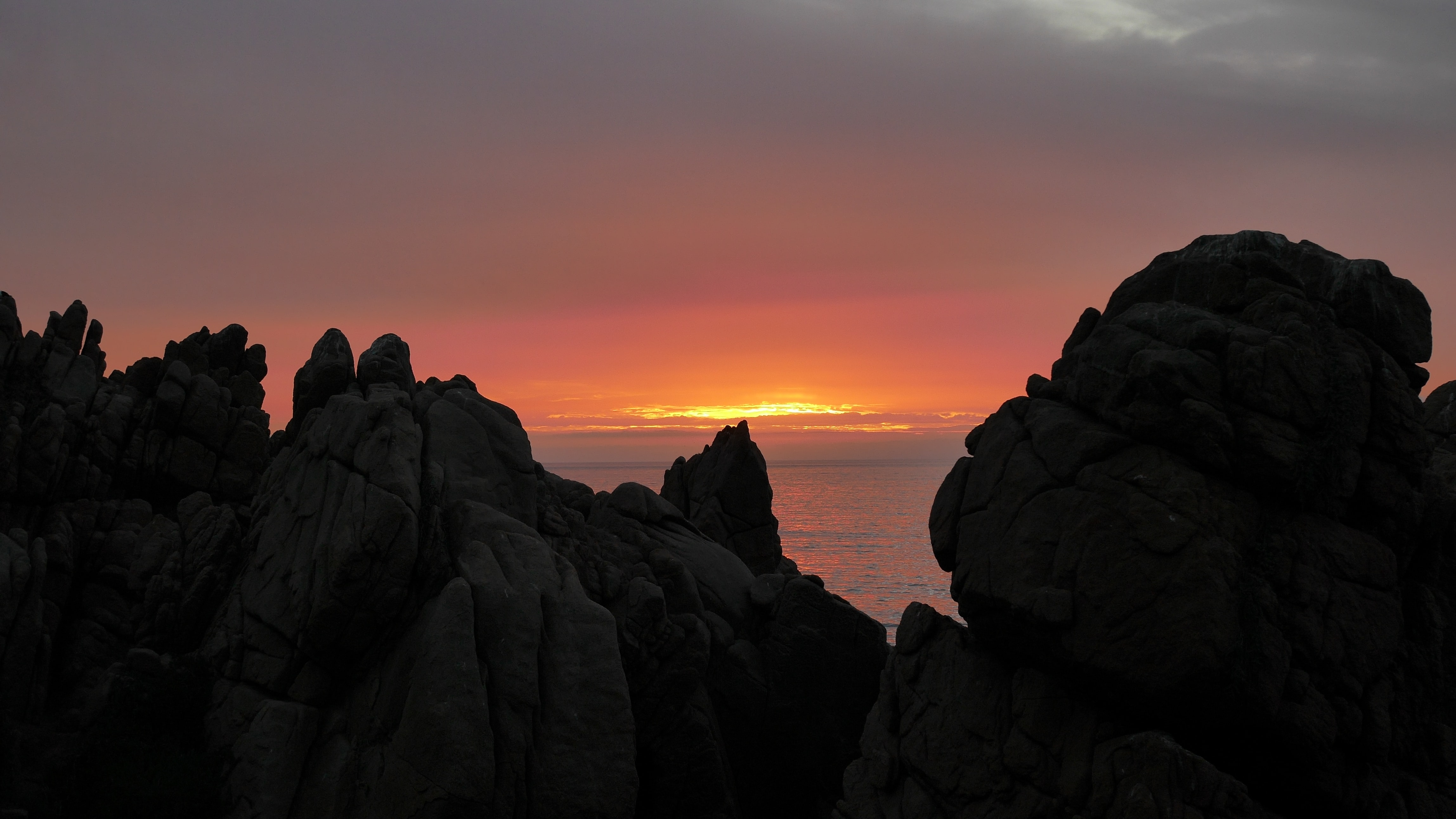 Large rocks and boulders by the sea, with view of the water and cloudy orange sunset between them