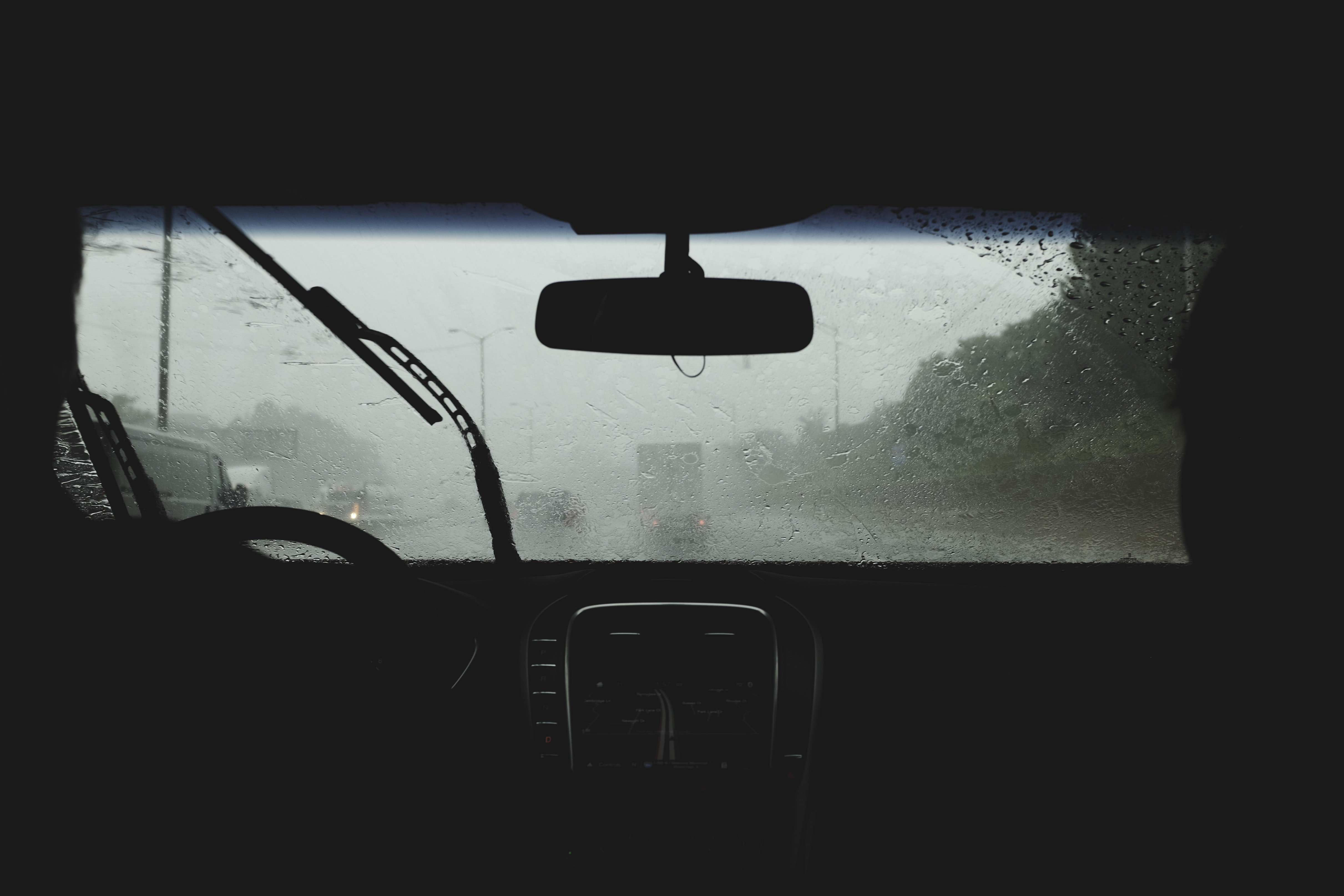 two person driving on rainy road