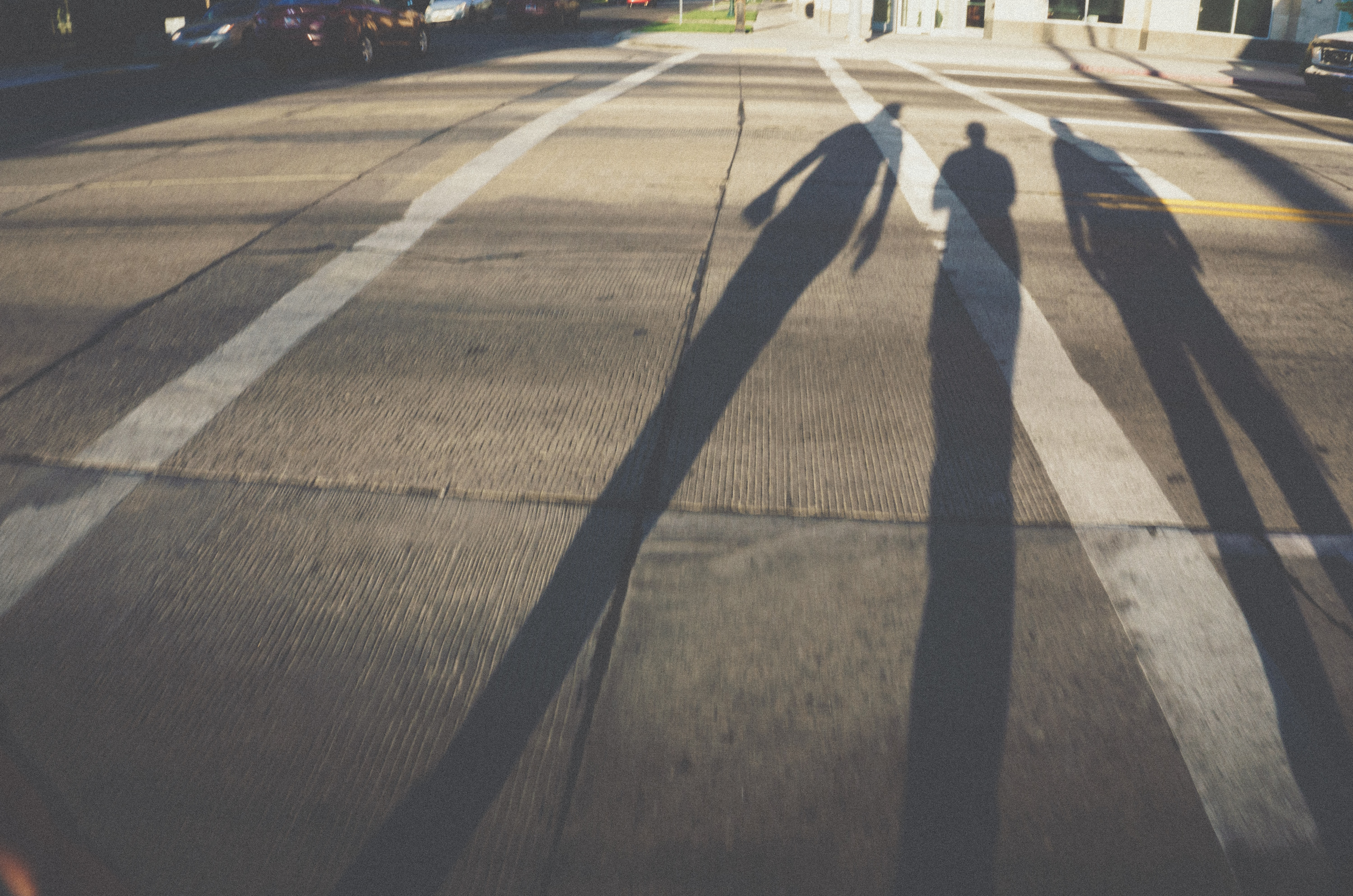 three shadow of persons on gray concrete pavement