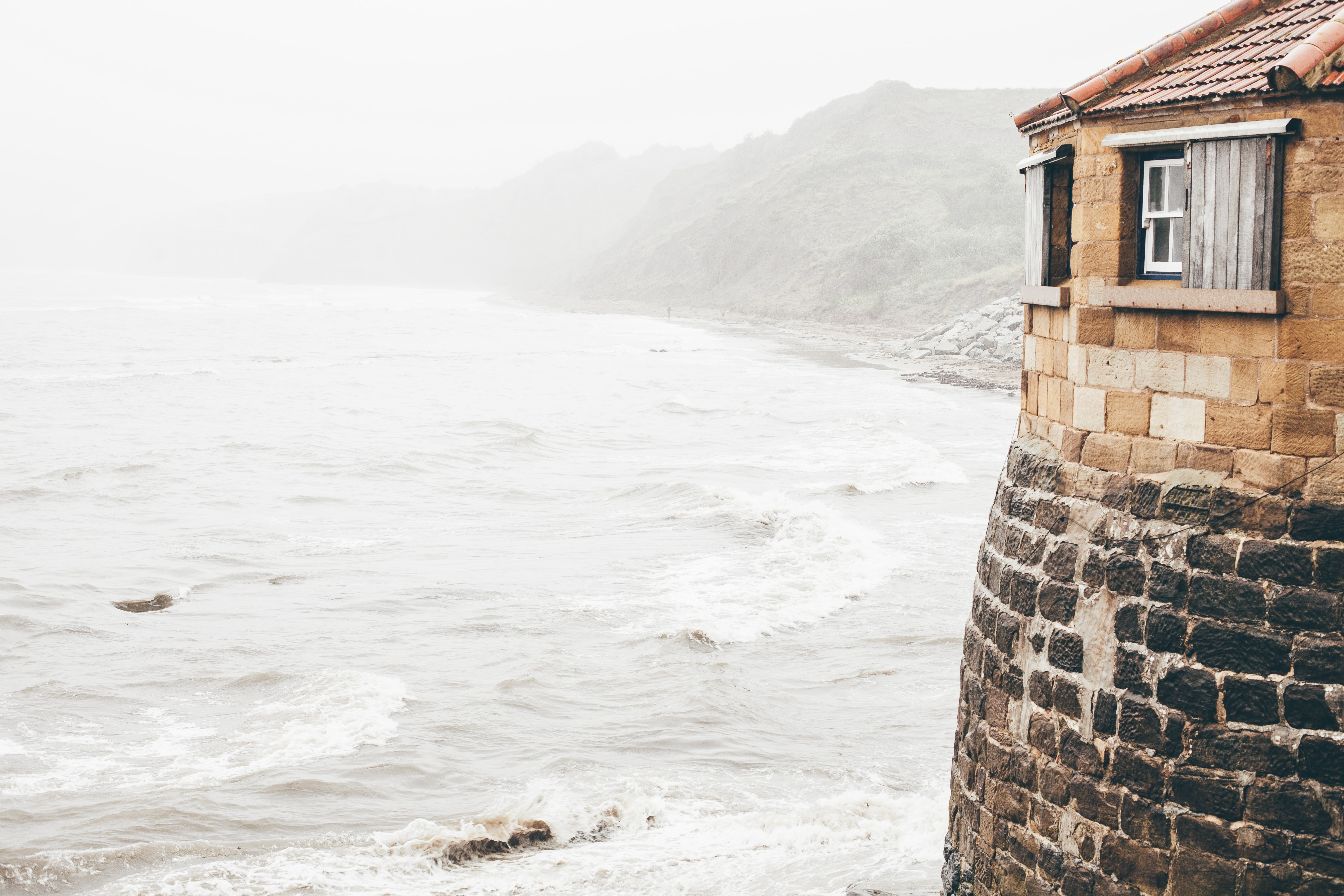 Brick building on the sea shore on a foggy morning