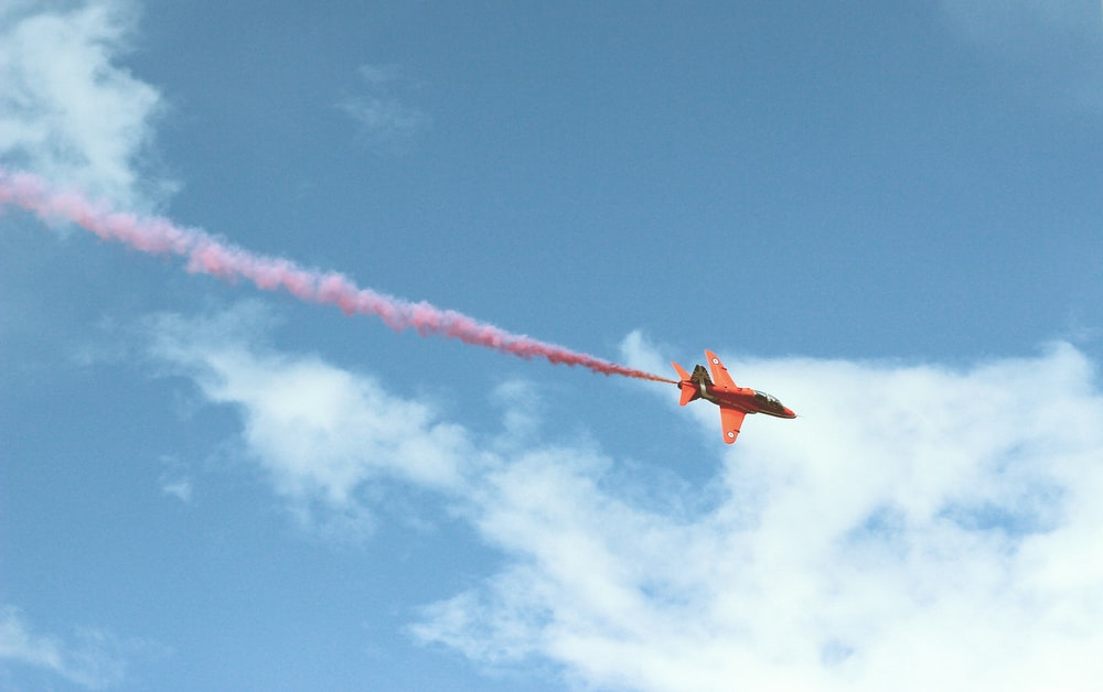 photo of jet plane with red smoke flying on air