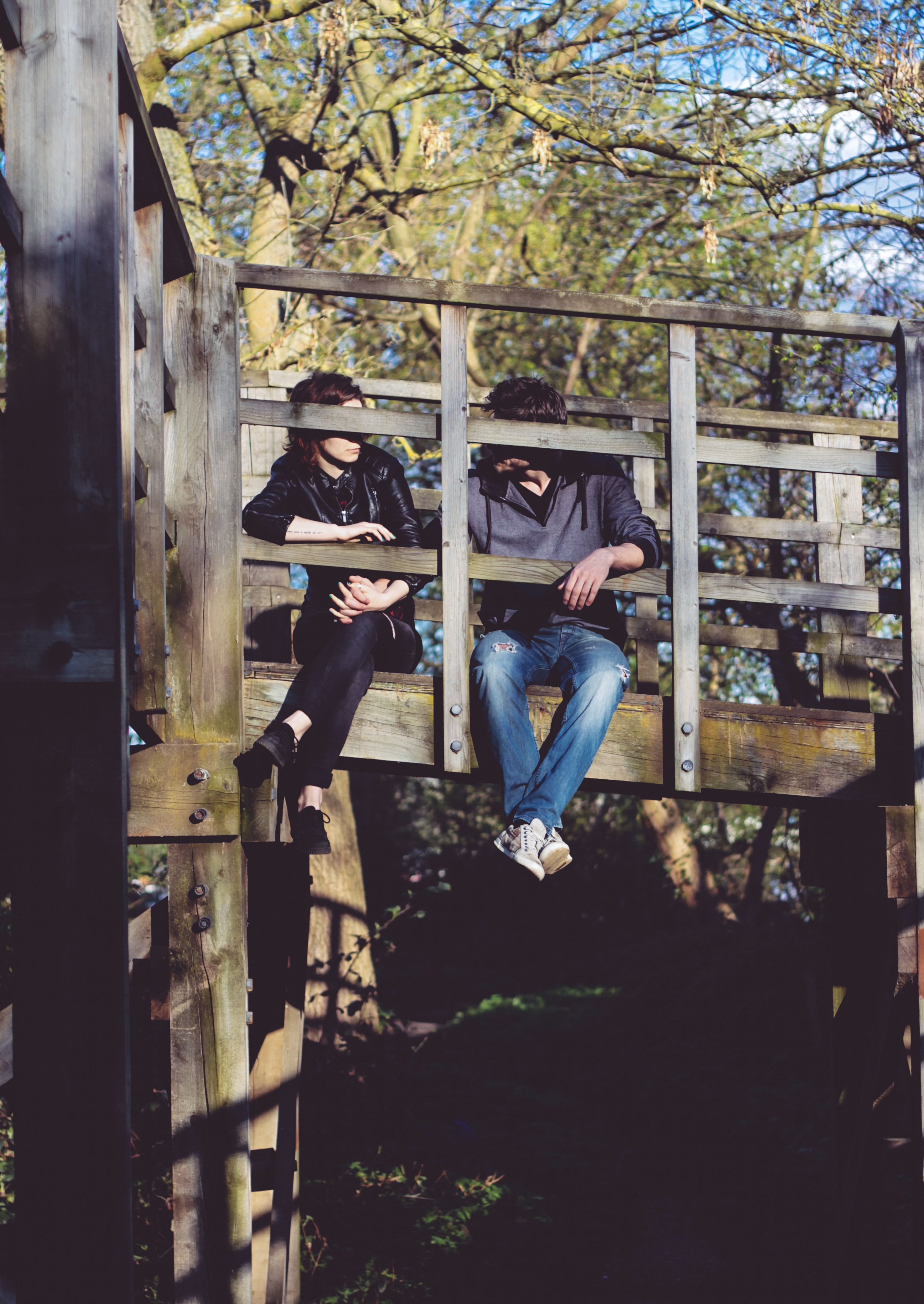 man and woman sitting on side of wooden bridge