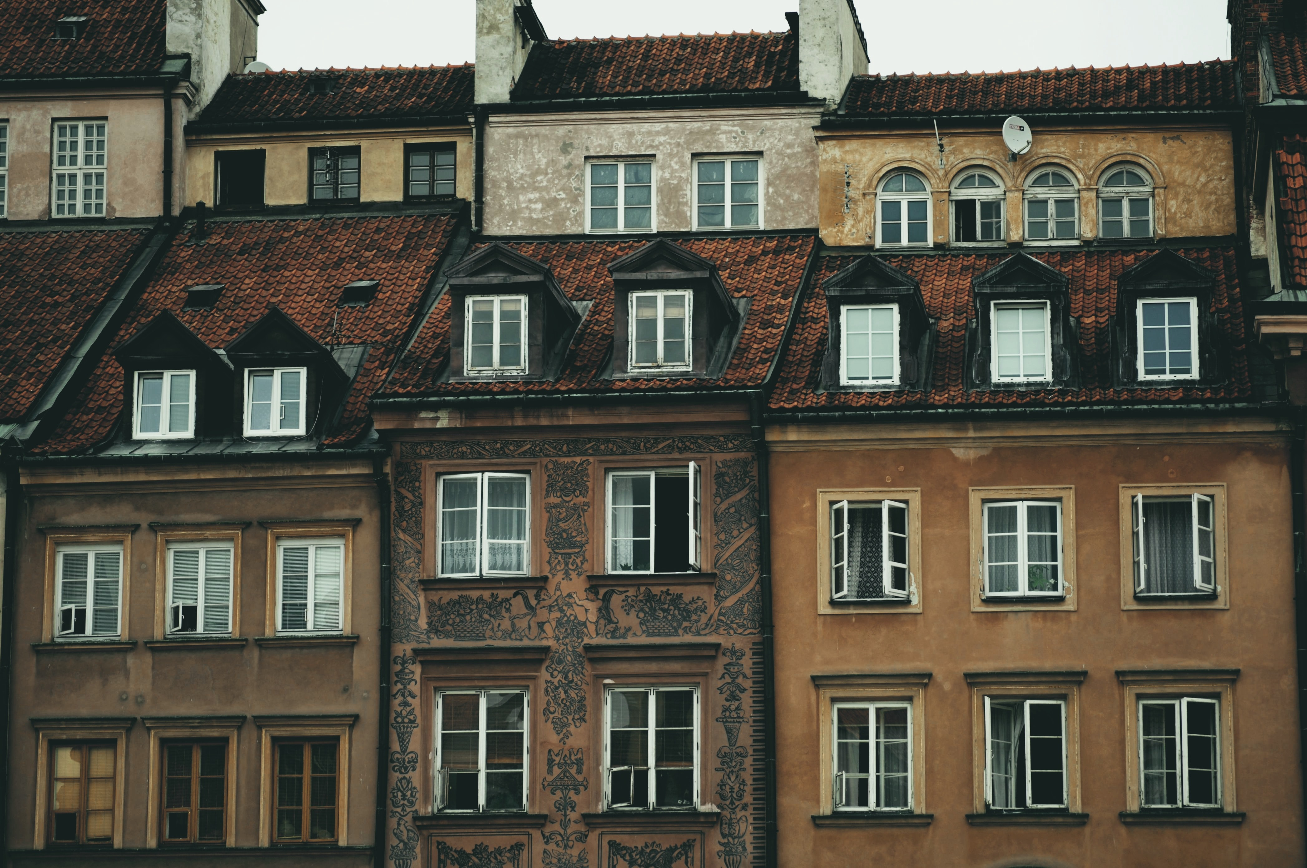 Two rows of stone and brick houses with brown roofs on an overcast day