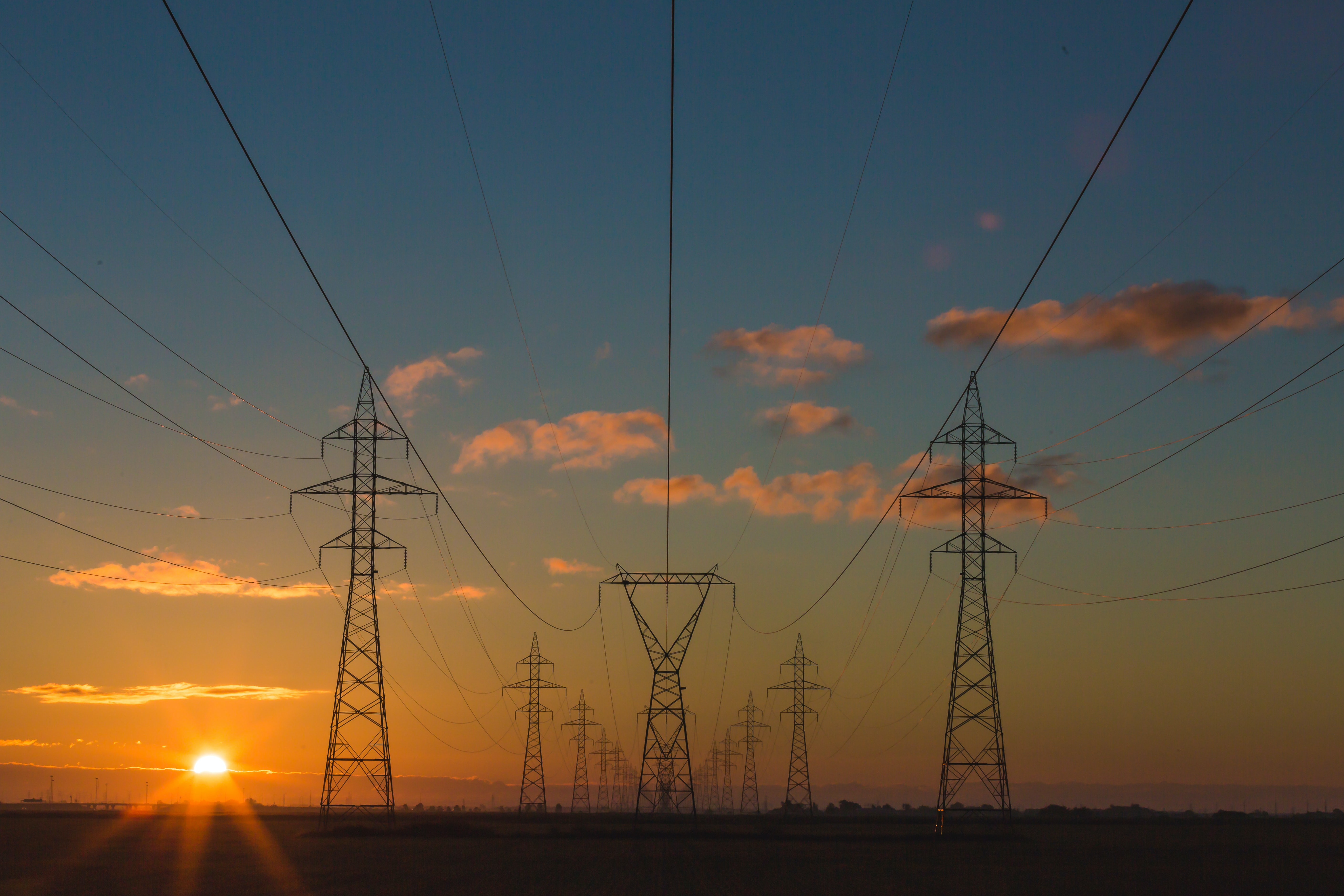 A large number of power pylons connected by power lines during sunset
