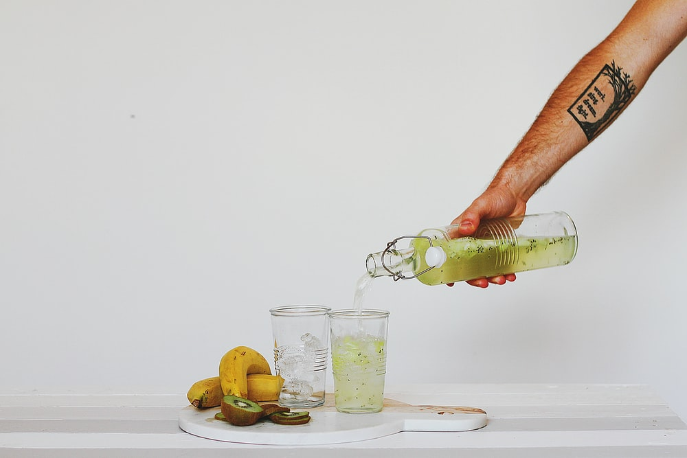 person pouring juice on glasses on table