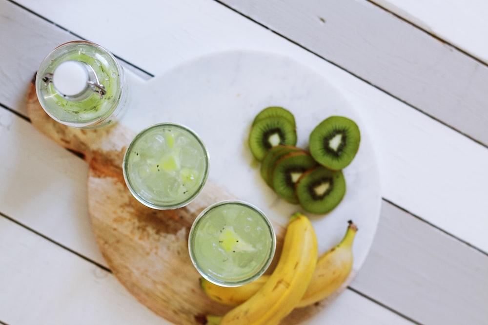 fruit juice cups beside yellow bananas on plate