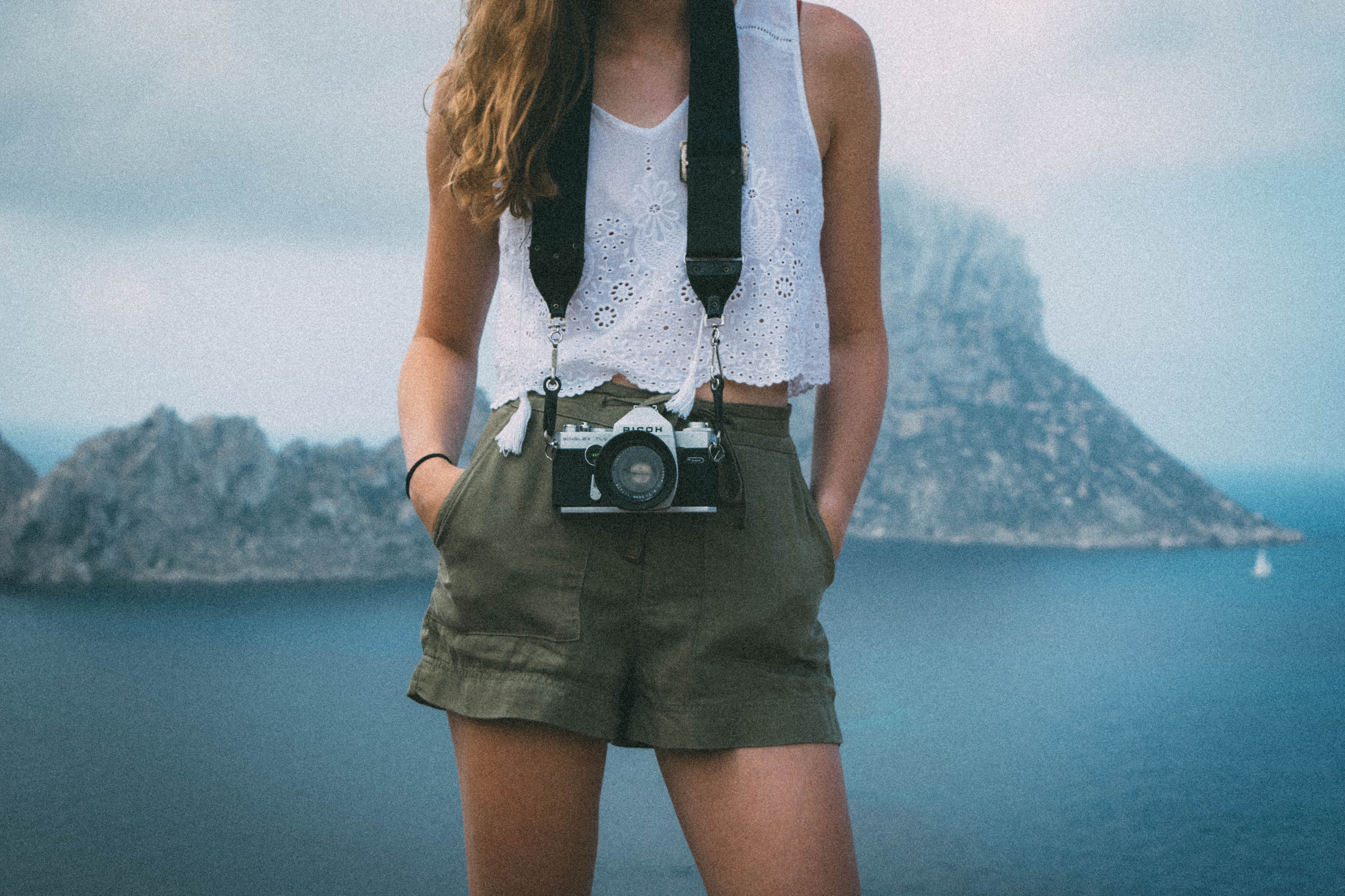 A woman wearing a white eyelet top, green shorts, and a camera hanging around her neck in Es Vedra
