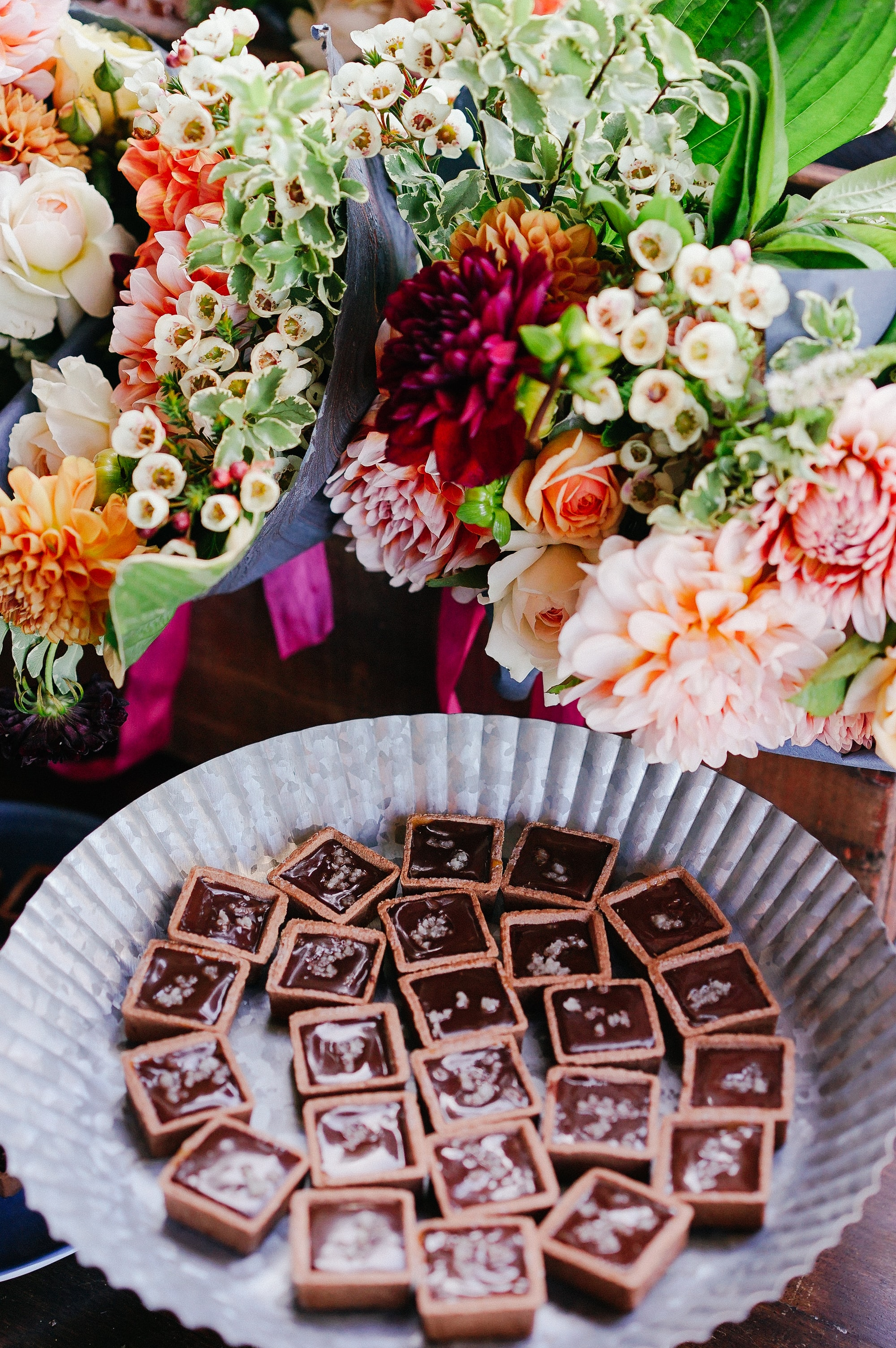 A paper plate with chocolate candy next to an arrangement of various flowers