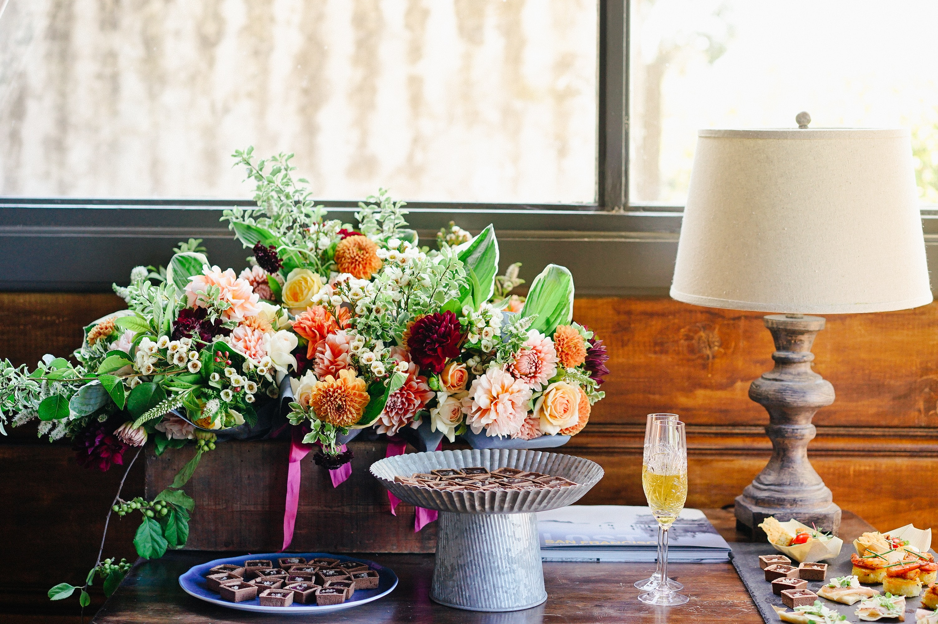 Sweet treats and champagne next to an impressive arrangement of flowers on a table