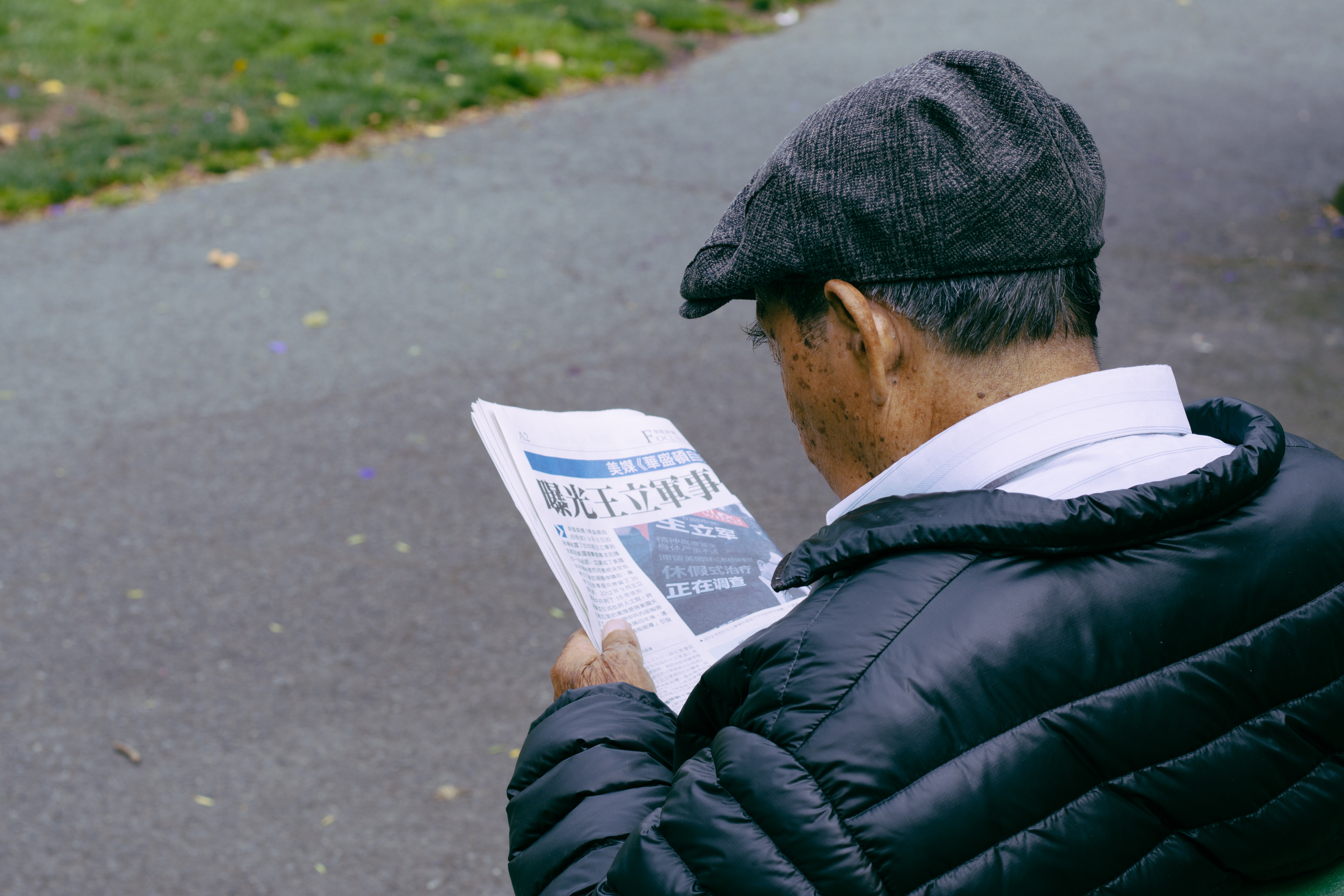 An older Chinese man stares down at a newspaper at Fisherman's Wharf