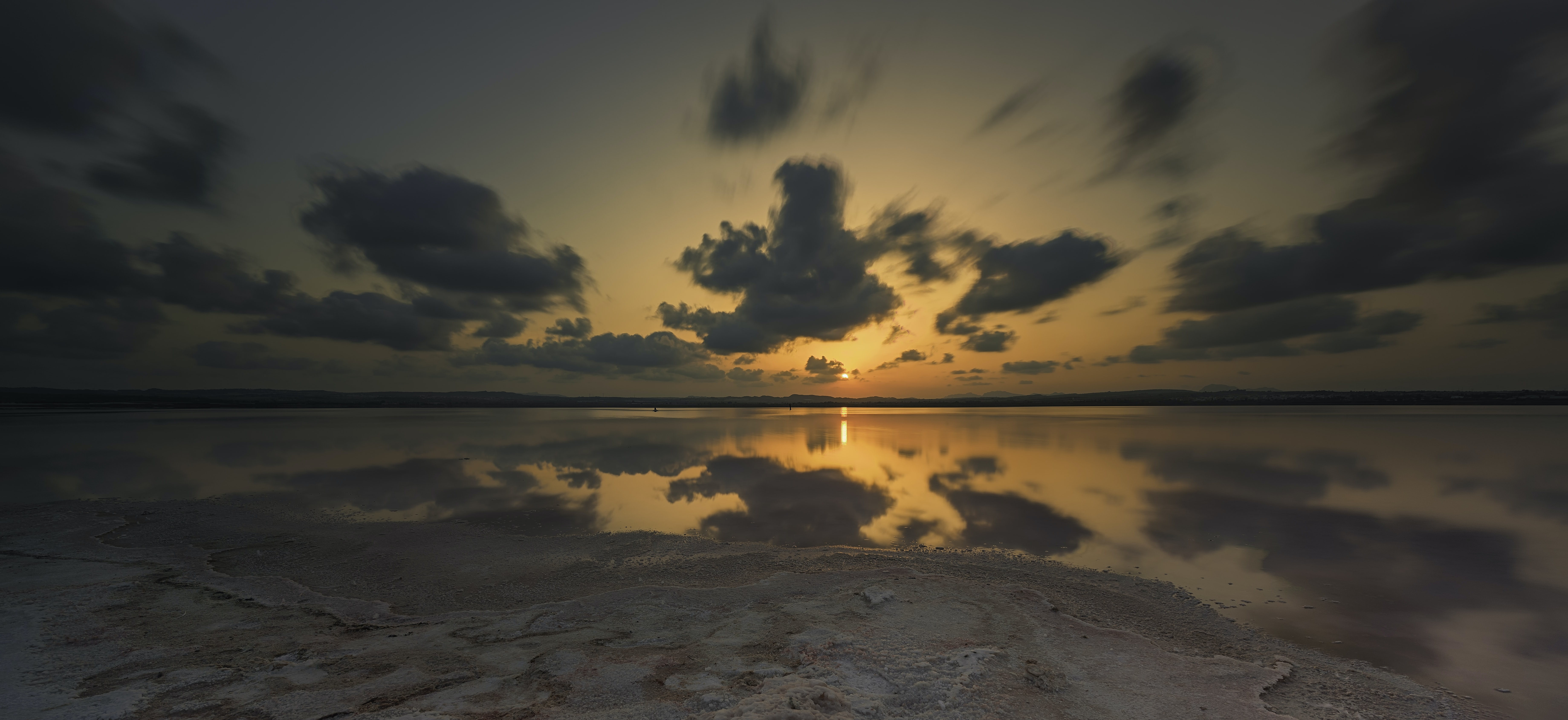 View of clouds drifting away from the sandy shoreline towards the sunset in Torrevieja, Spain