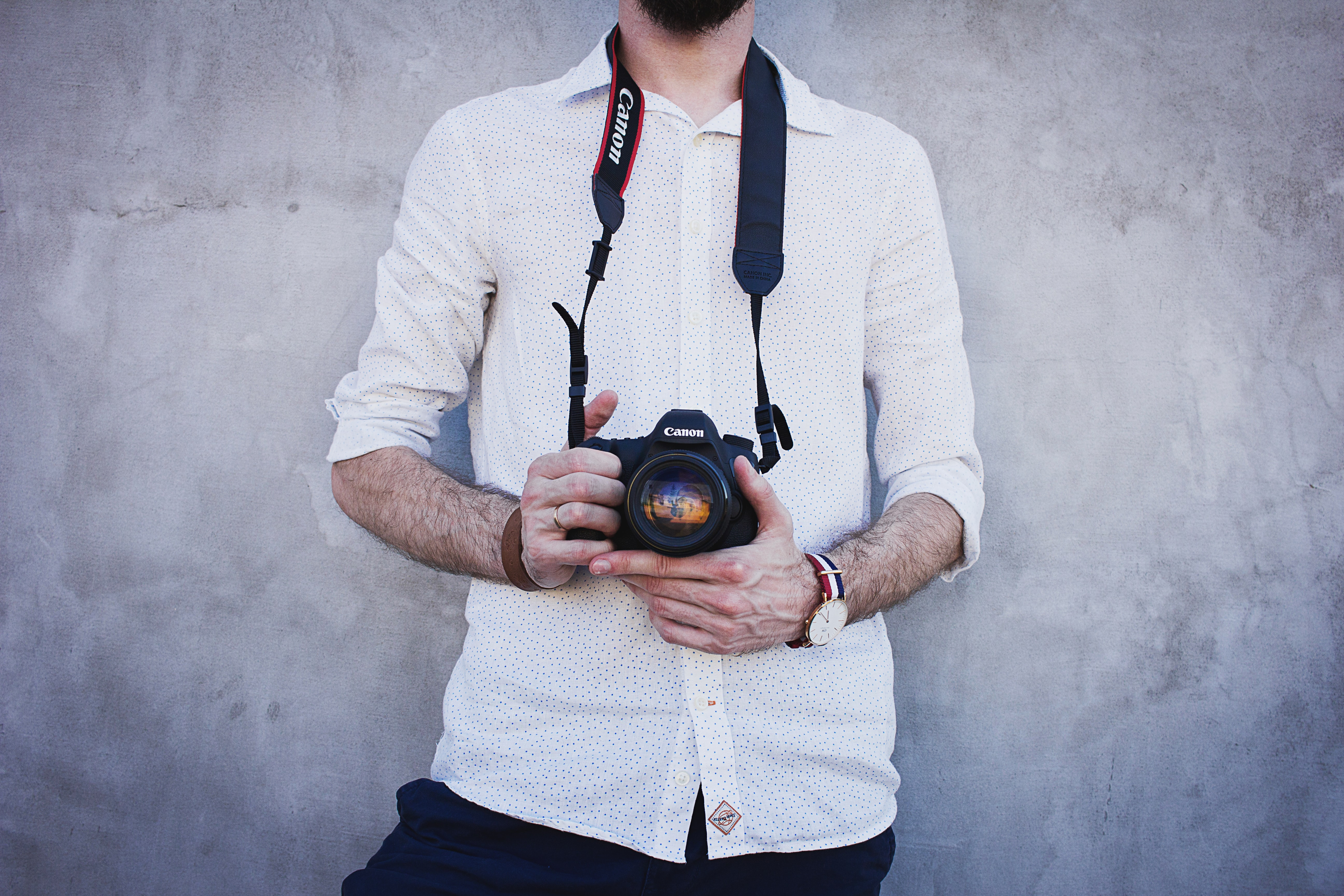 A man in a white polka dotted shirt holding a Canon camera in Olsztyn