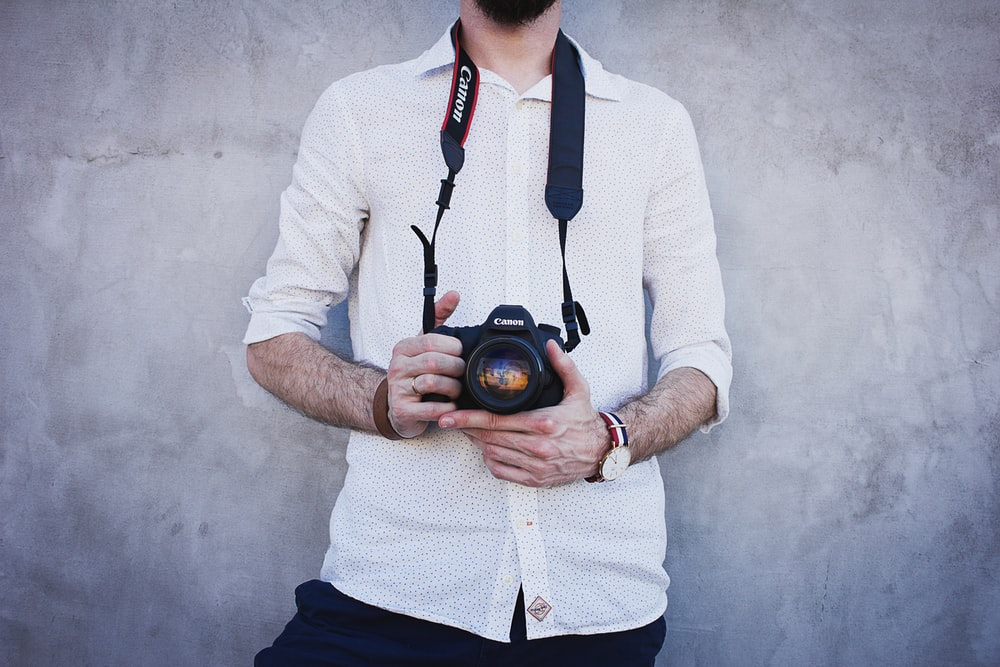 man in white dress shirt holding Canon DSLR camera