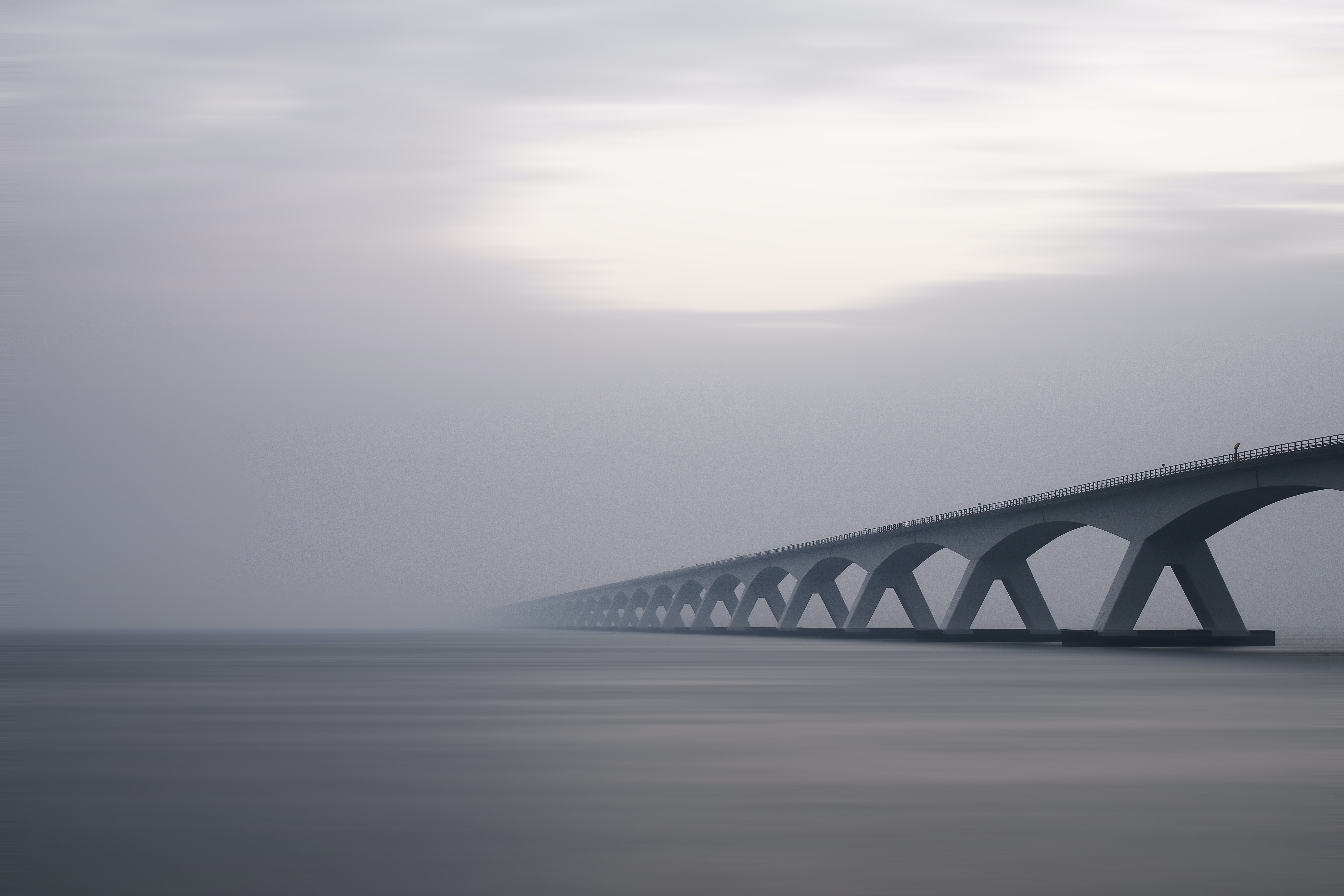 A gray day by a bridge over calm foggy waters