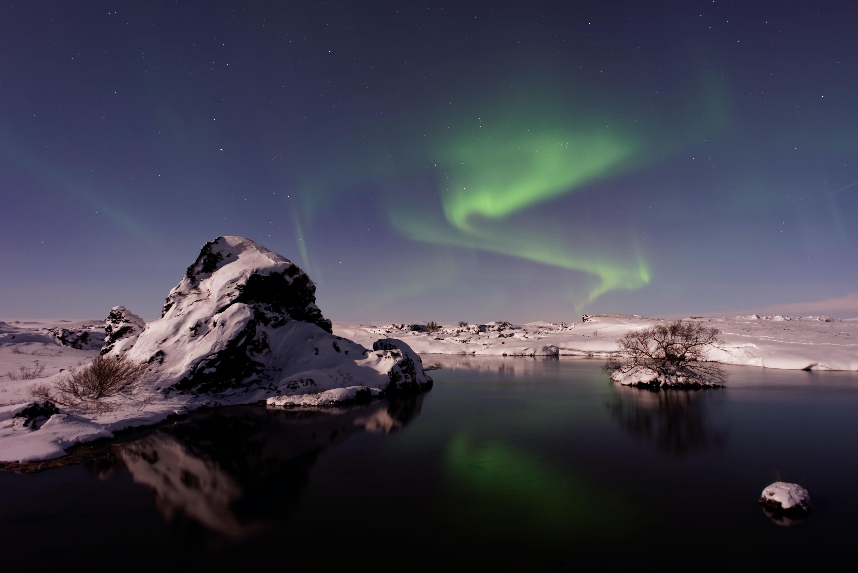 river beside snowfield under aurora borealis